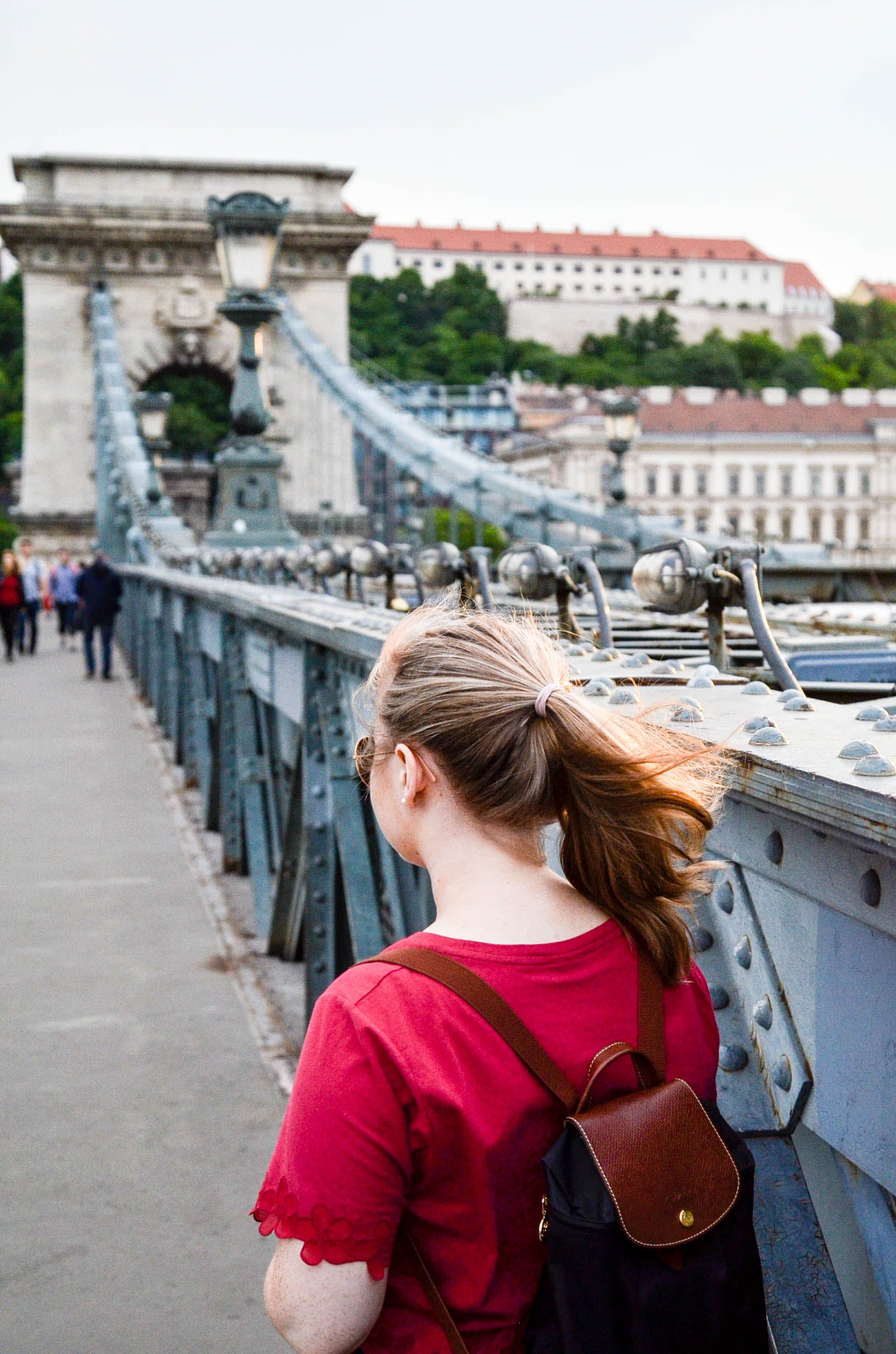Woman Wearing Brown Leather Backpack Standing on Bridge Photo Taken