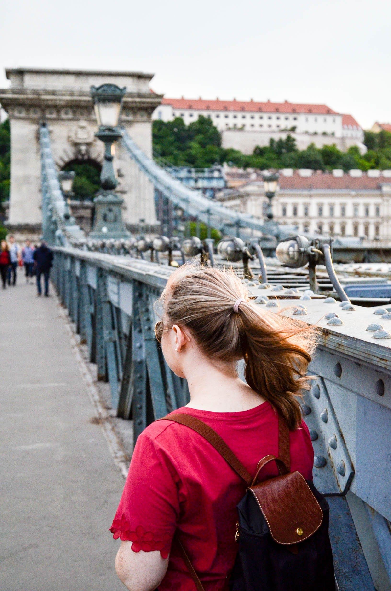 Woman Wearing Brown Leather Backpack Standing on Bridge Photo Taken