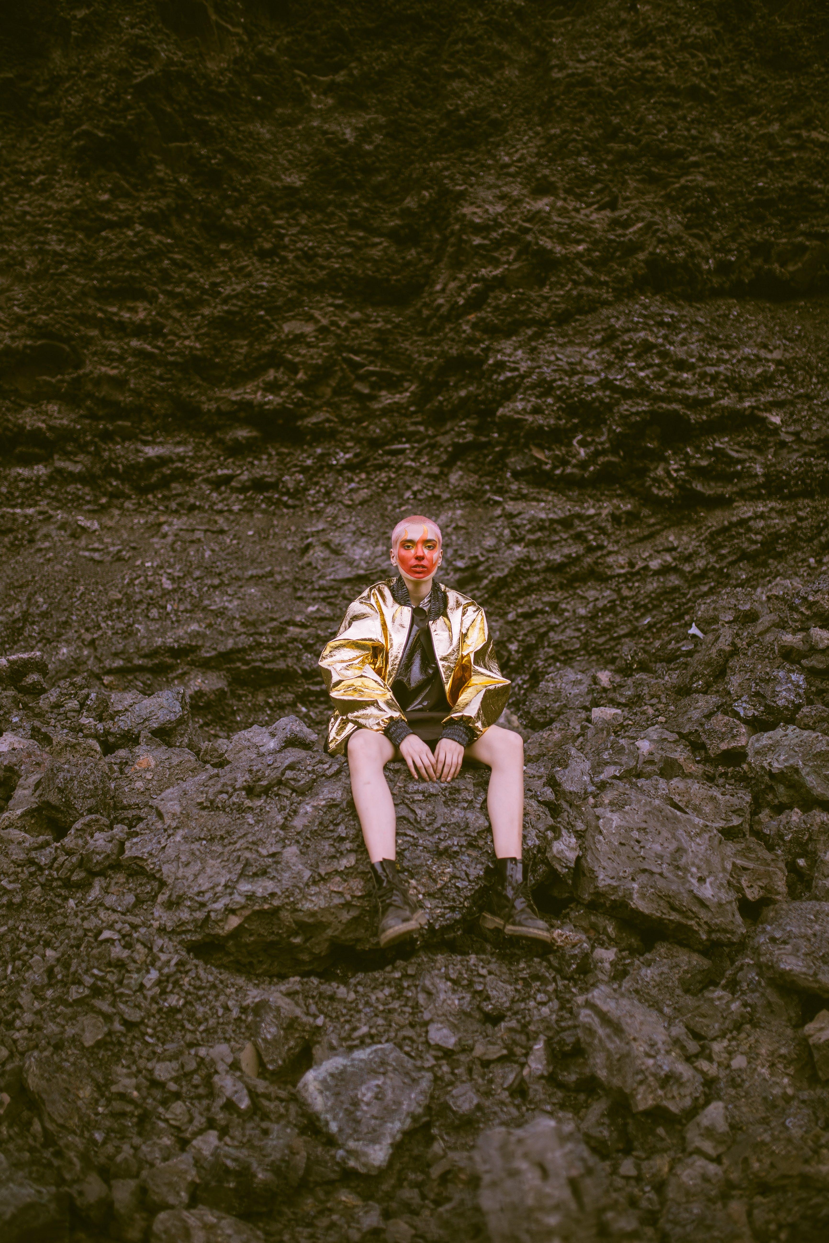 Man Wearing Gold Jacket Sitting on Stone