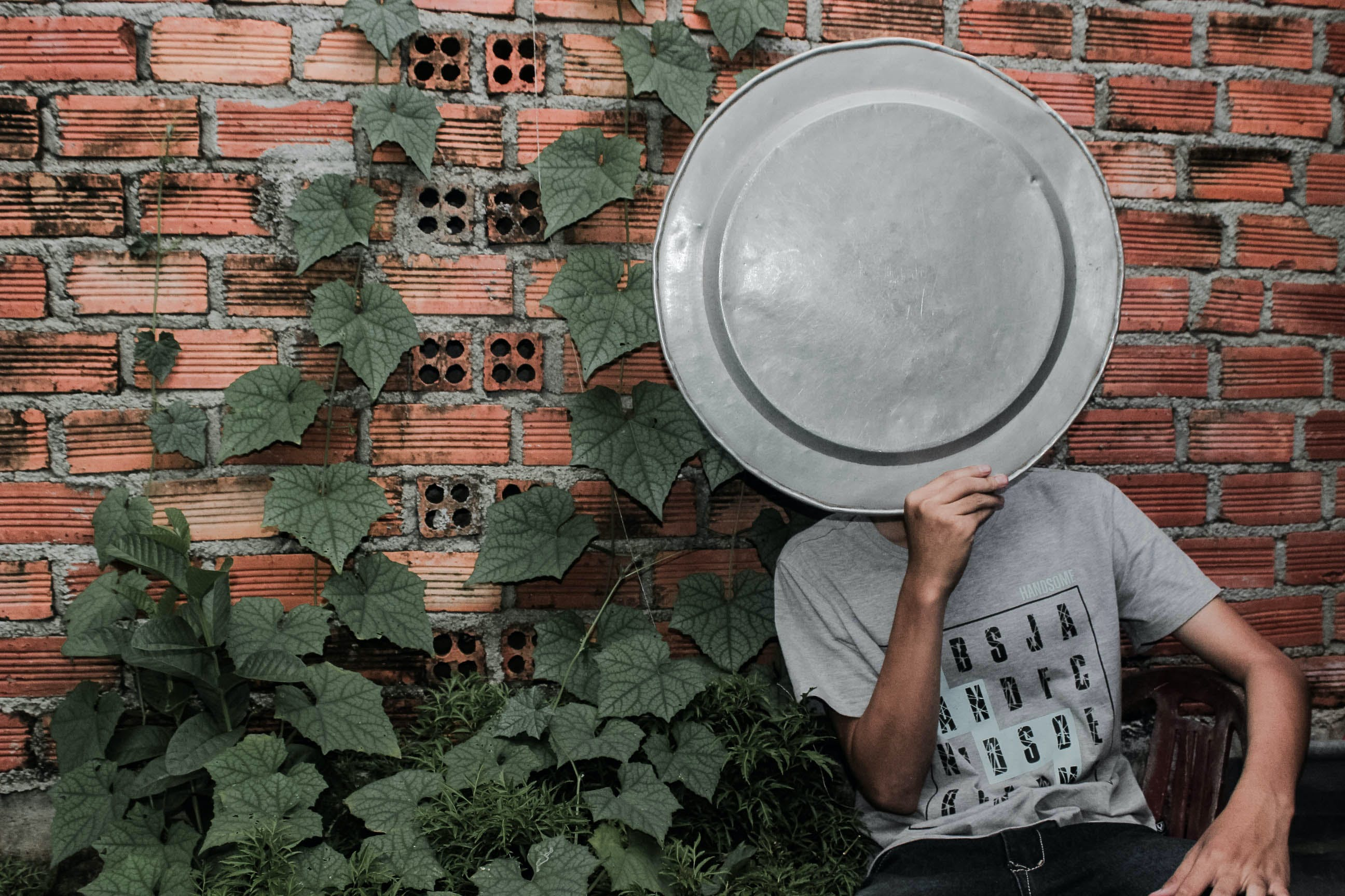 Person Wearing Gray Crew-neck T-shirt holding a tray on the face next to a brick wall