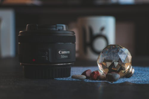 Close-Up Photography of Camera Lens Near Gem