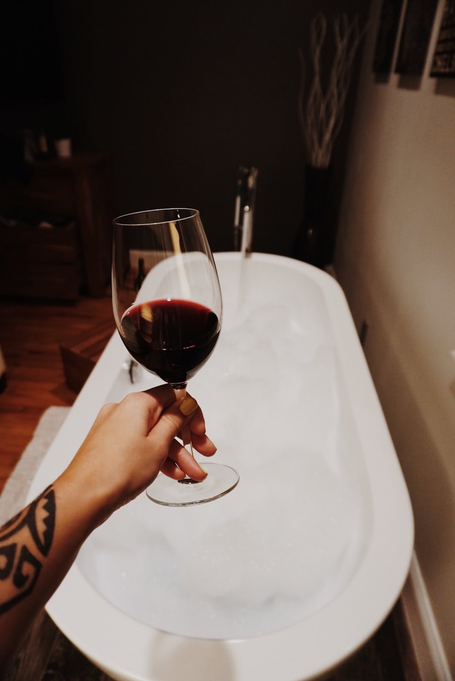 Person Holding Wine Glass Filled With Red Liquid Substance