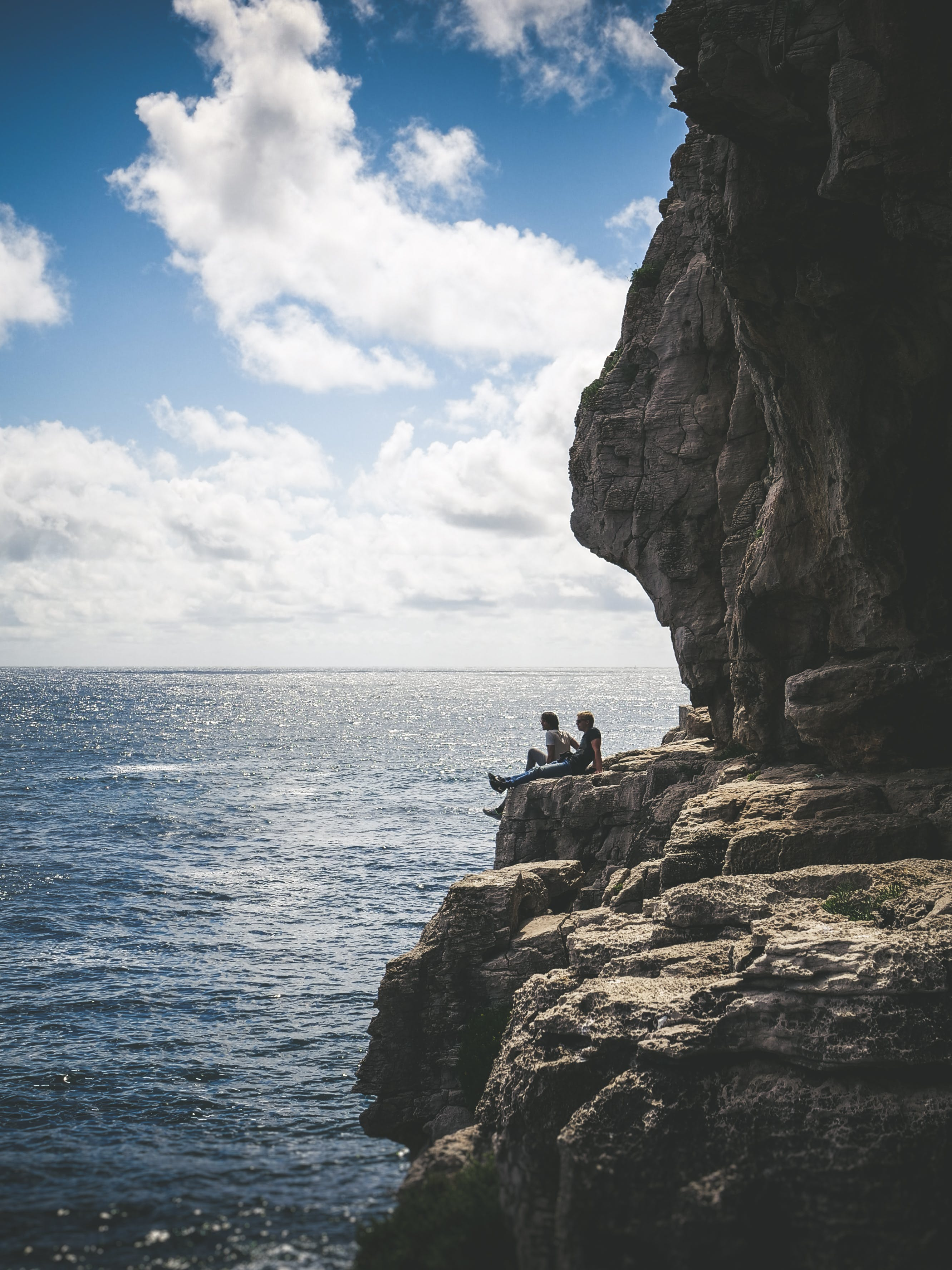 Two People Sitting By The Cliff