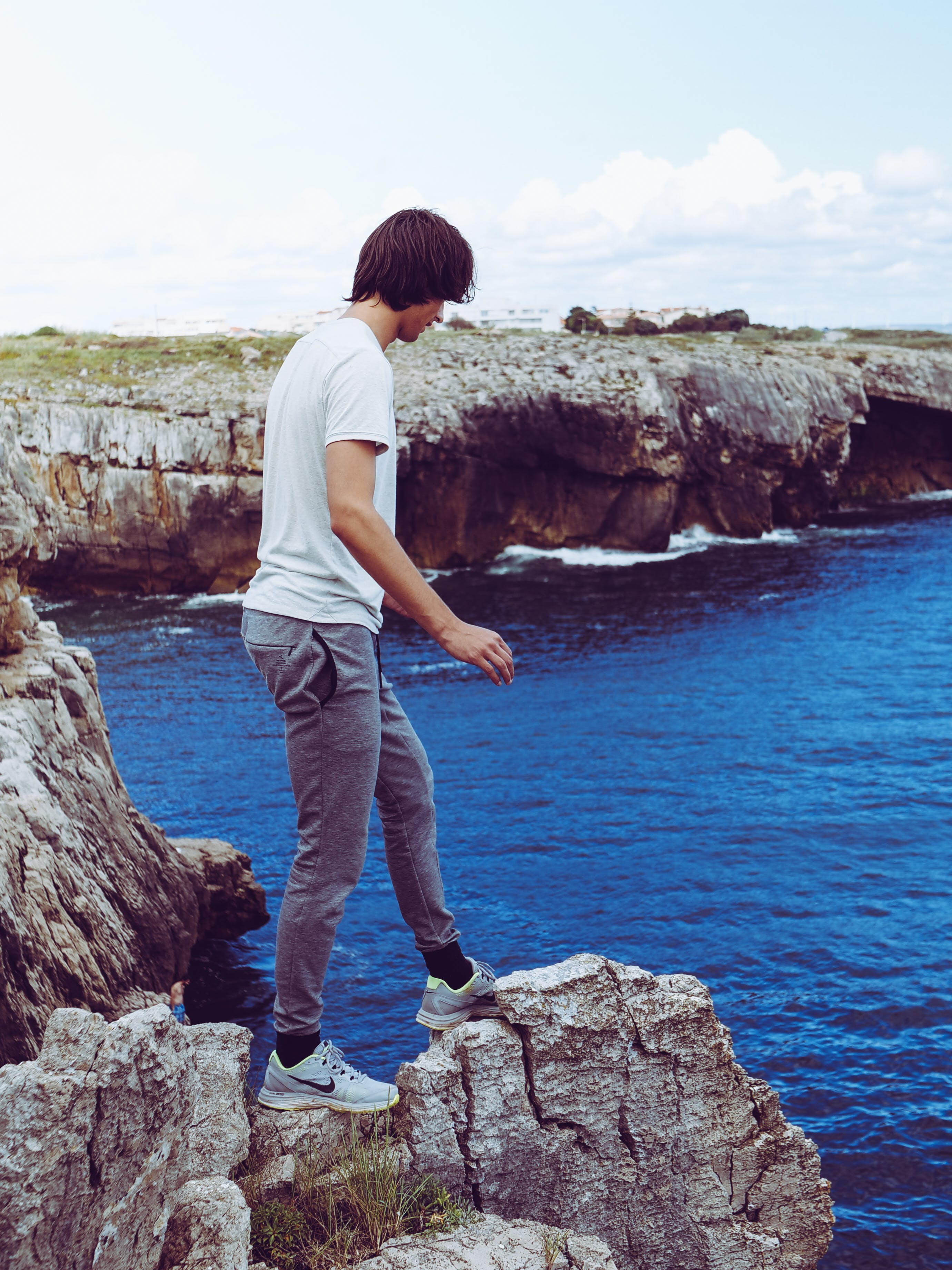 Man In White Shirt And Grey Pants Standing On Cliff