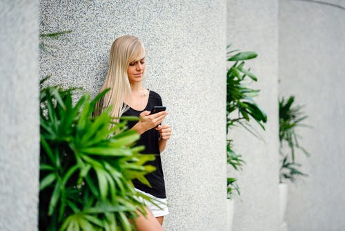 Woman Wearing Black Scoop-neck Shirt Standing in Front on Concrete Column Holding Smartphone