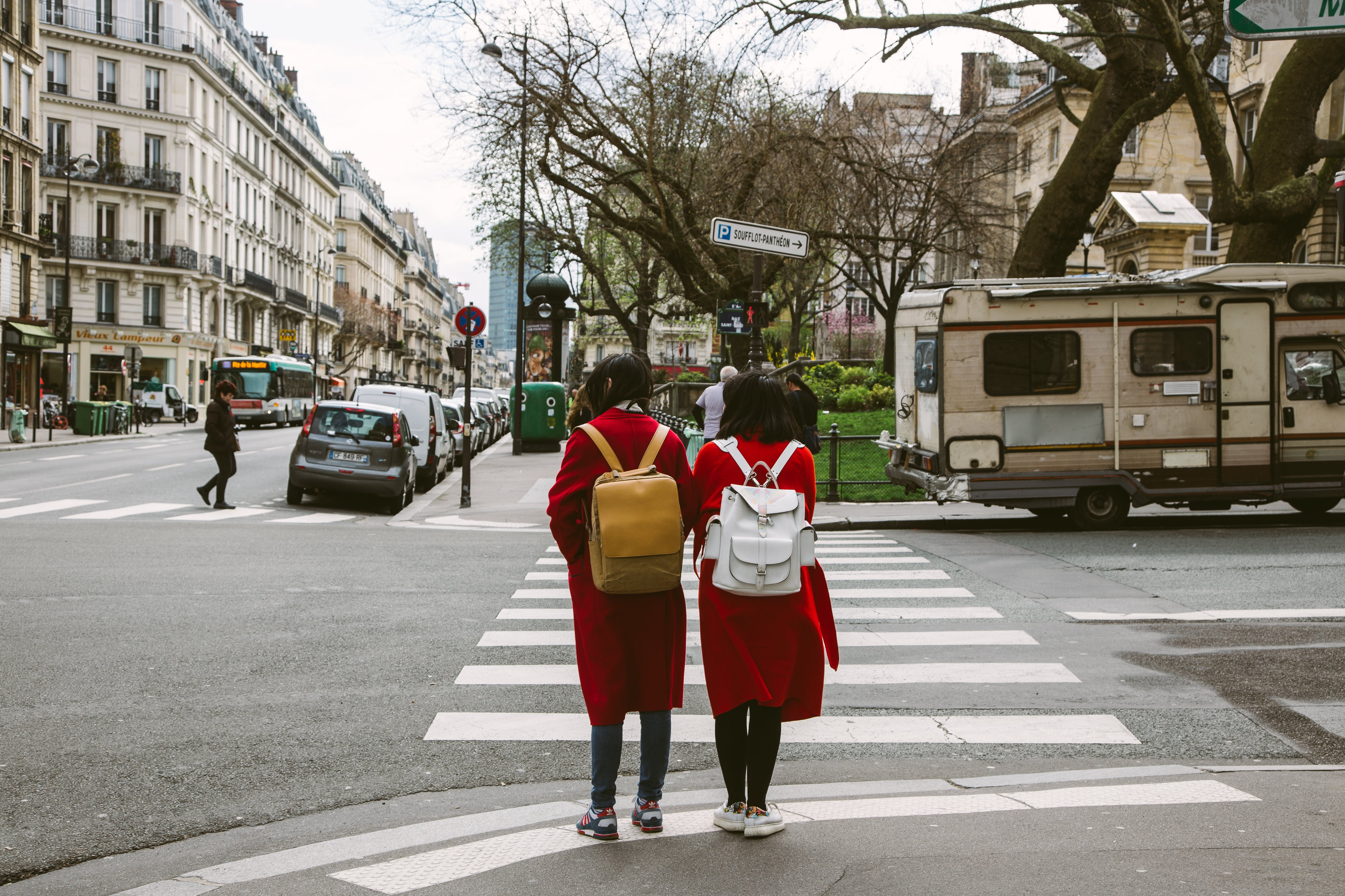 Two Women Wearing Red Coats With Backpacks