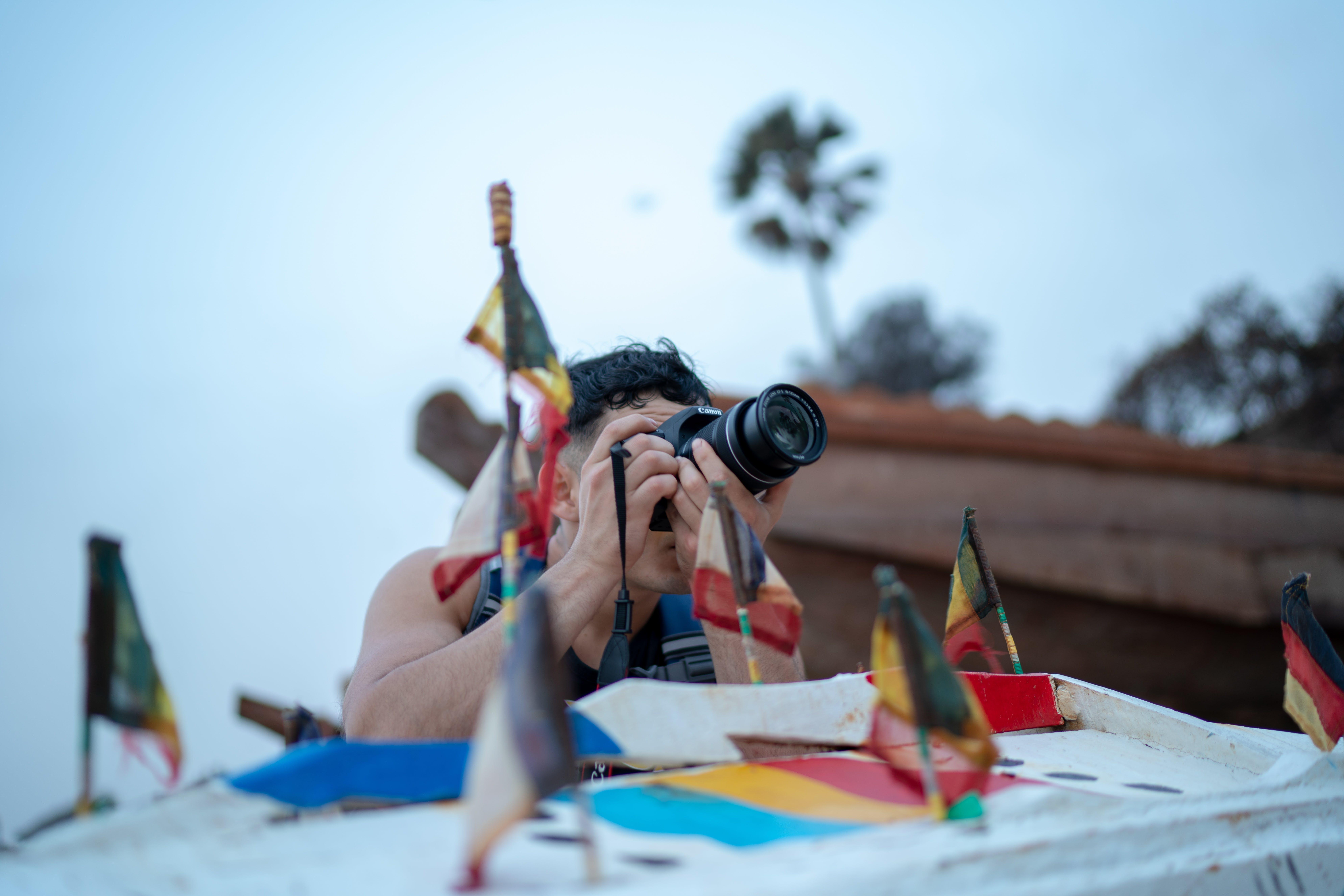 Man Taking Photo Using Dslr Camera Near Country Flag Miniatures