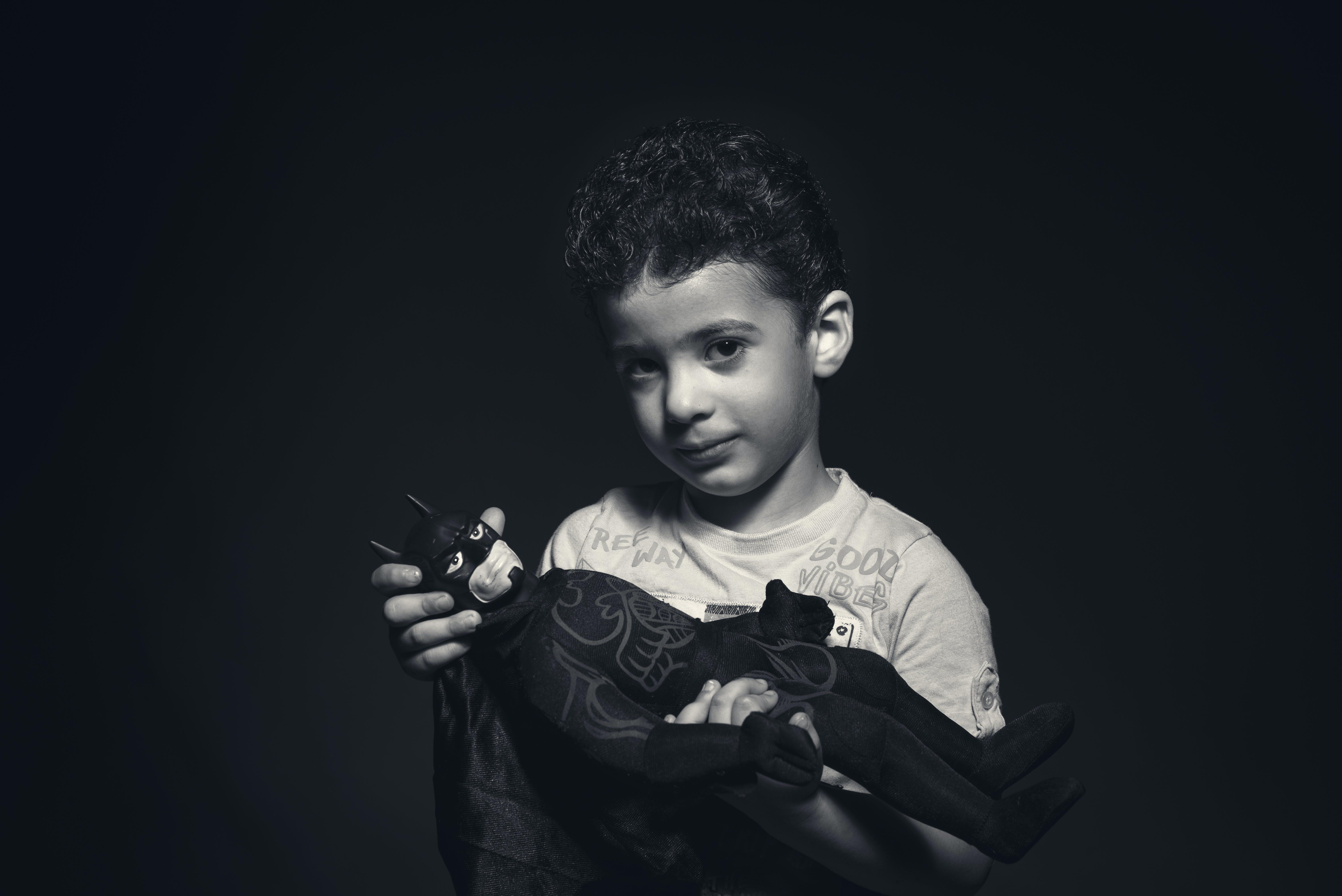 Grayscale Photo of a boy Holding Batman Plush Toy
