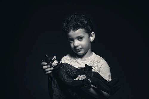 Grayscale Photo of a boy Holding Batman Plush Toy