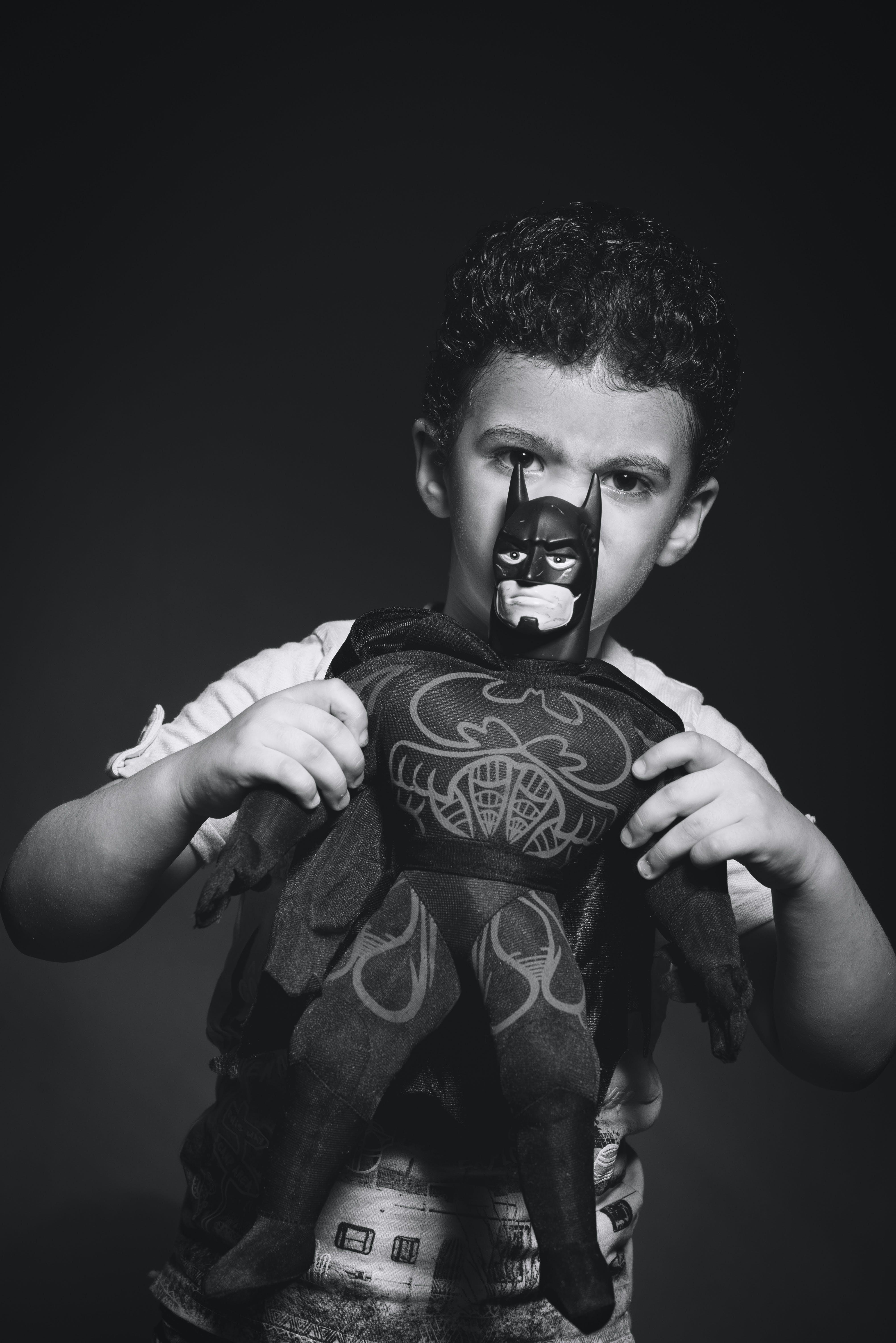 Grayscale Photo of Boy Holding Batman Plush Toy