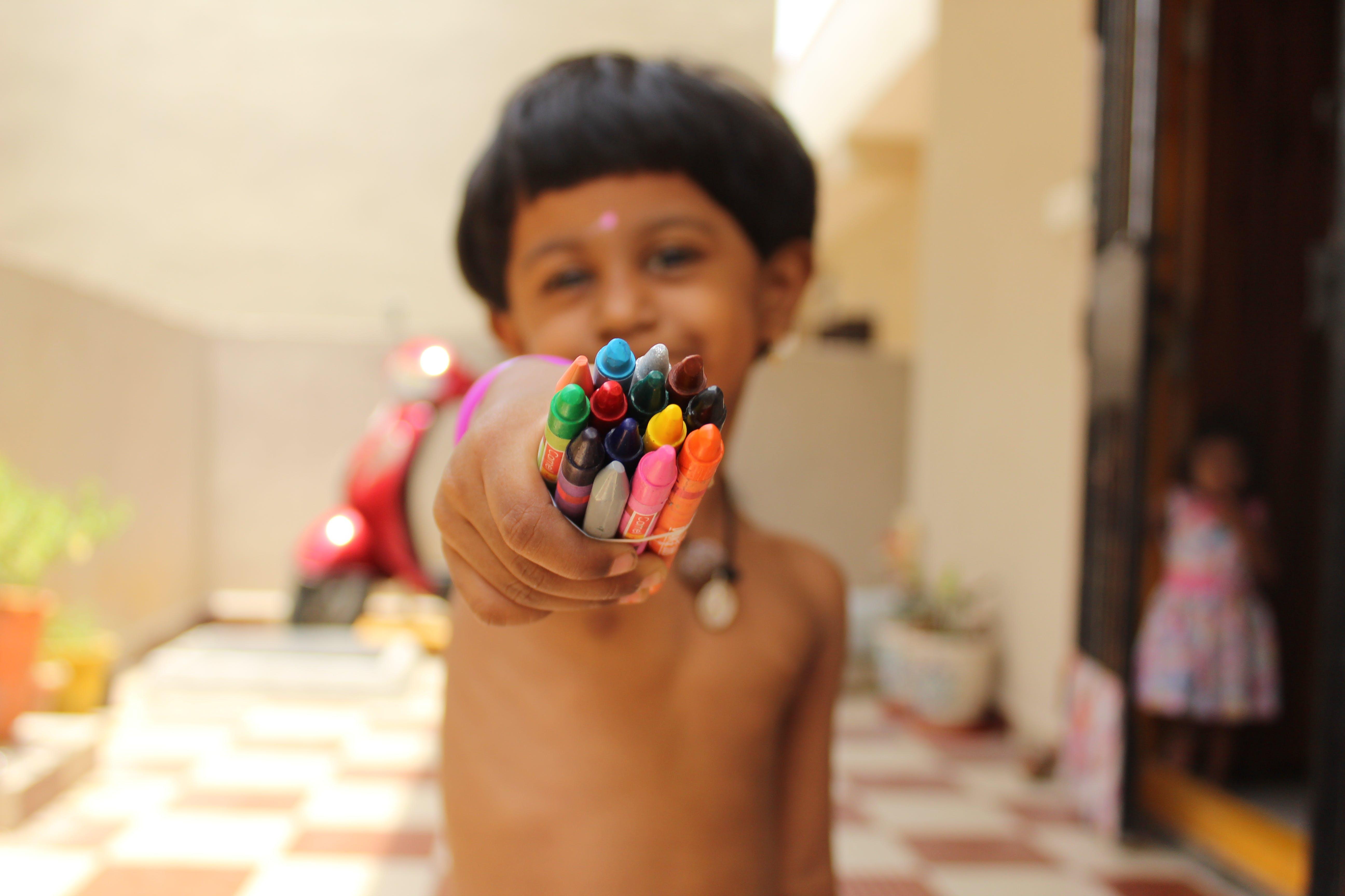 Boy Holding Crayons