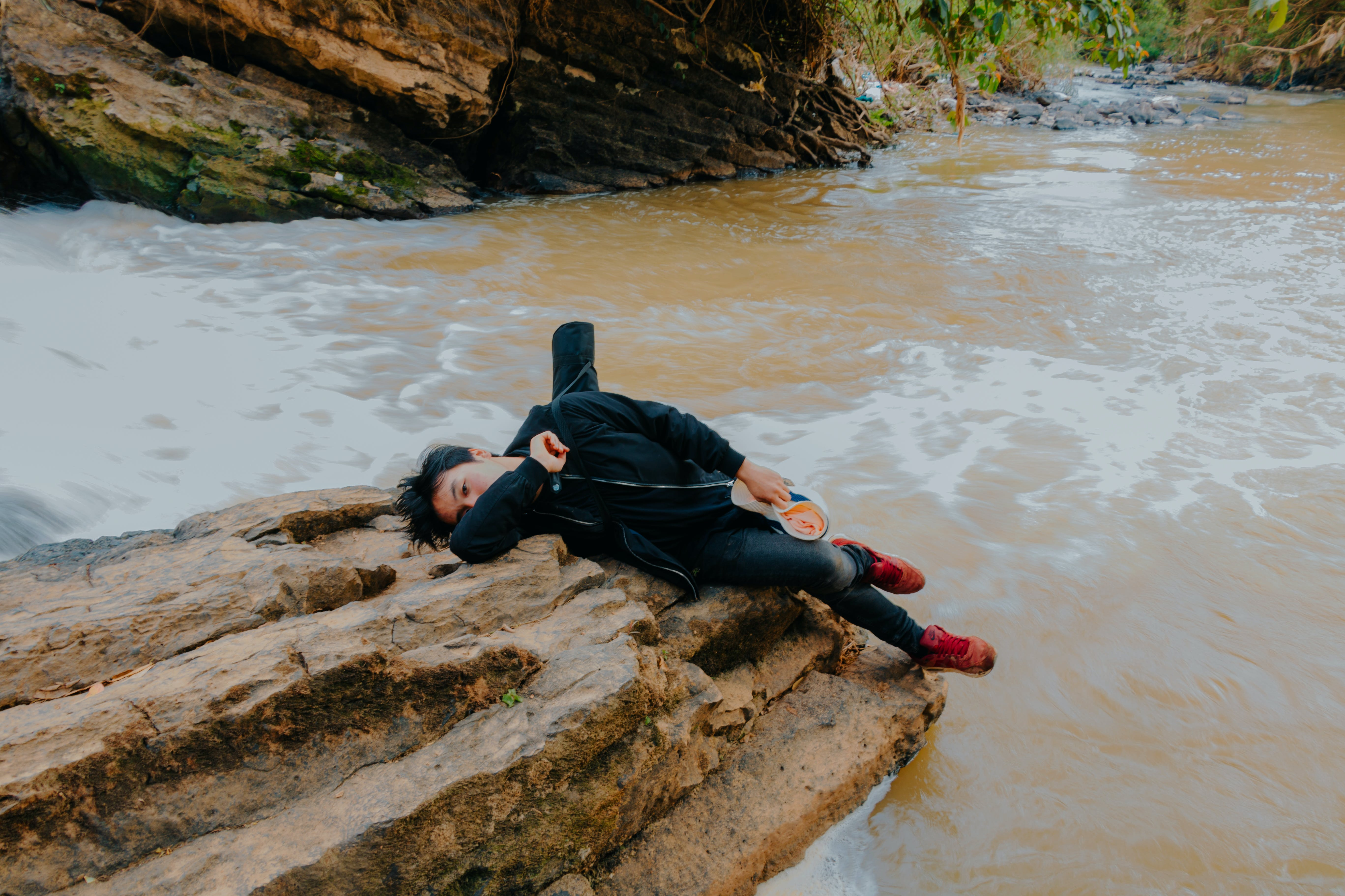 Photo of Man Lying on Rock at River