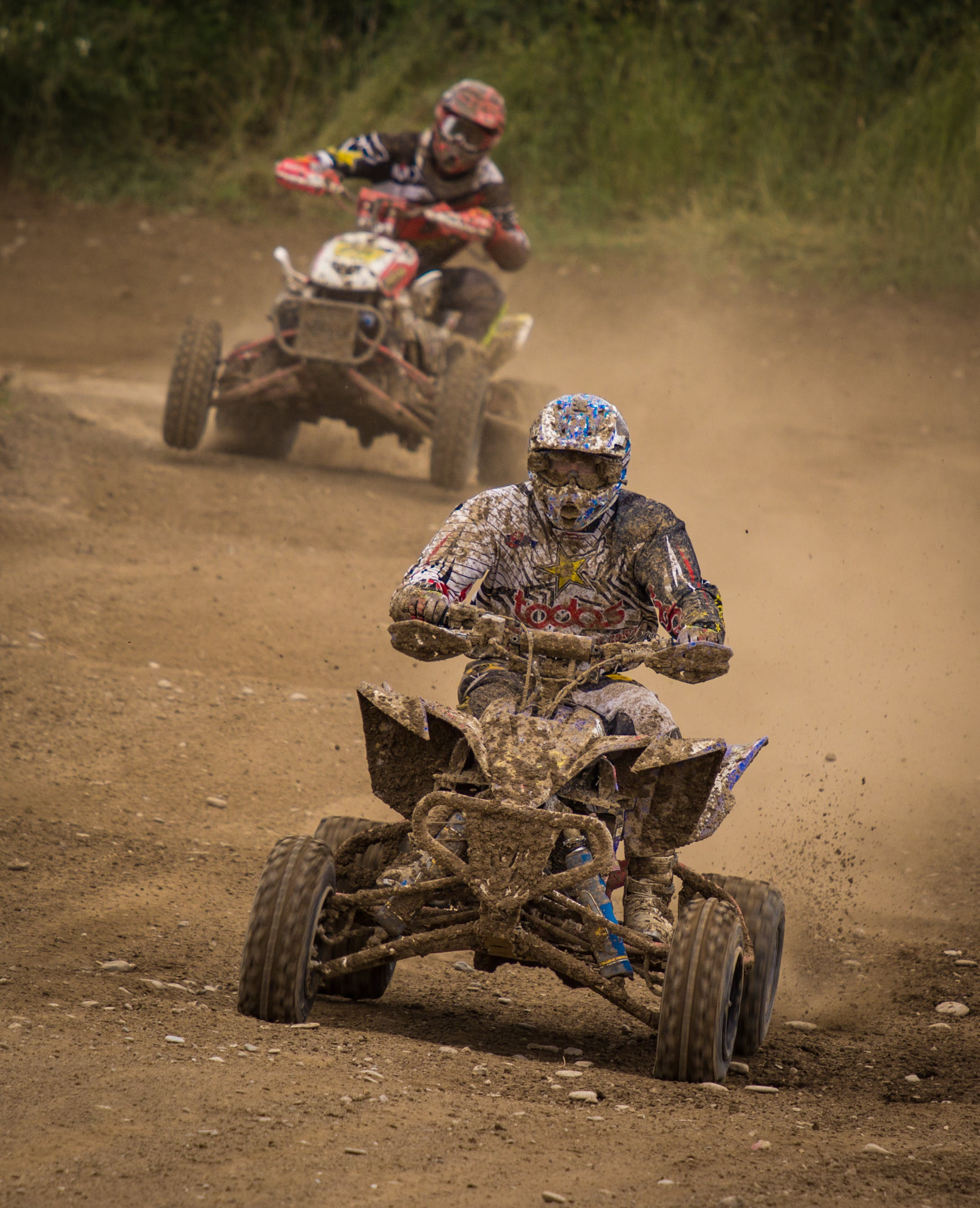 Man Wearing White Racing Outfit Stained With Mud Riding on Stained Mud Atv
