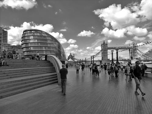 Grayscale Photo of People Walking Near Tower Bridge at London