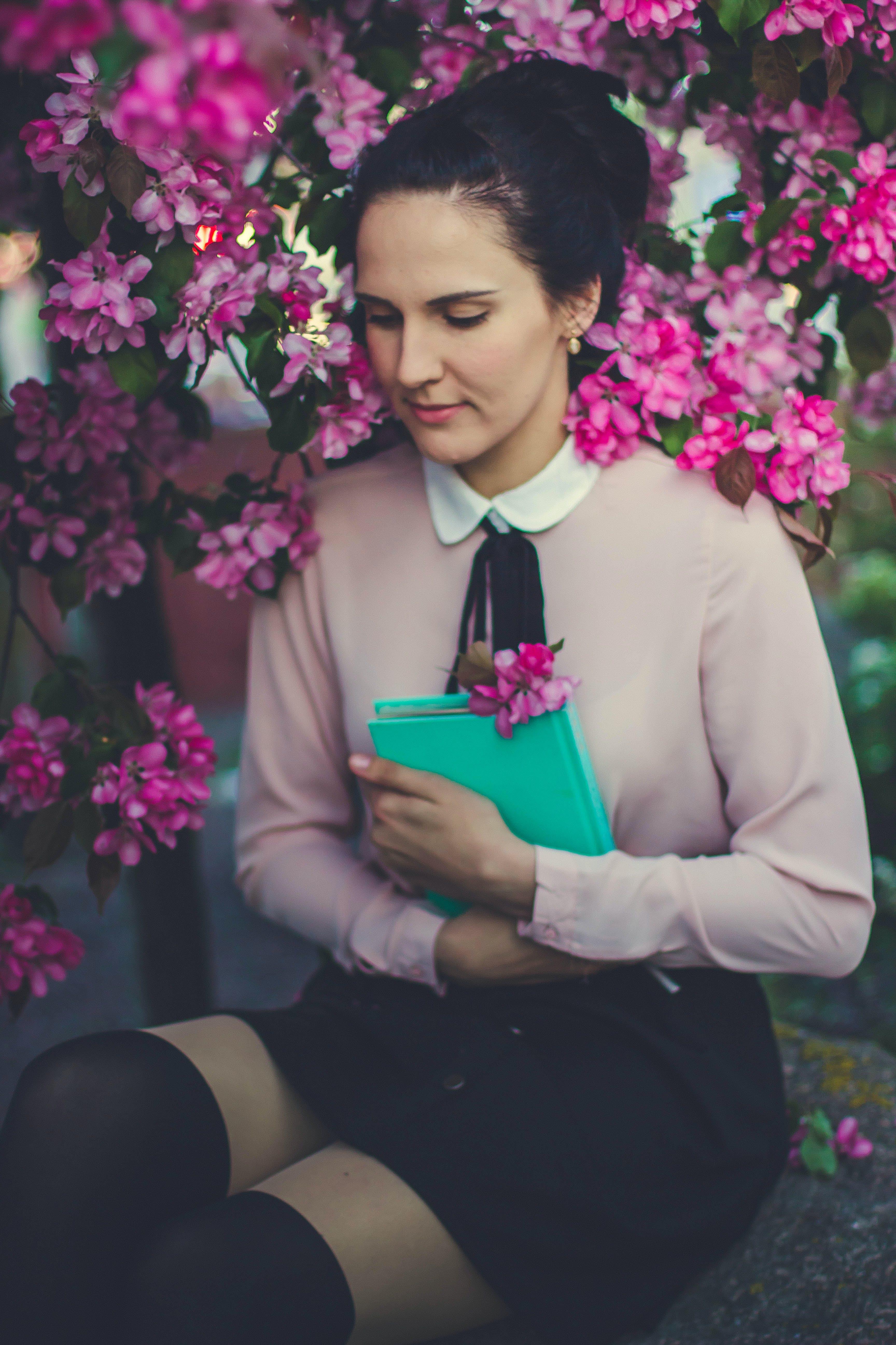 Woman Wearing Beige Long Sleeve Shirt Sitting Beside Purple Petaled Flower