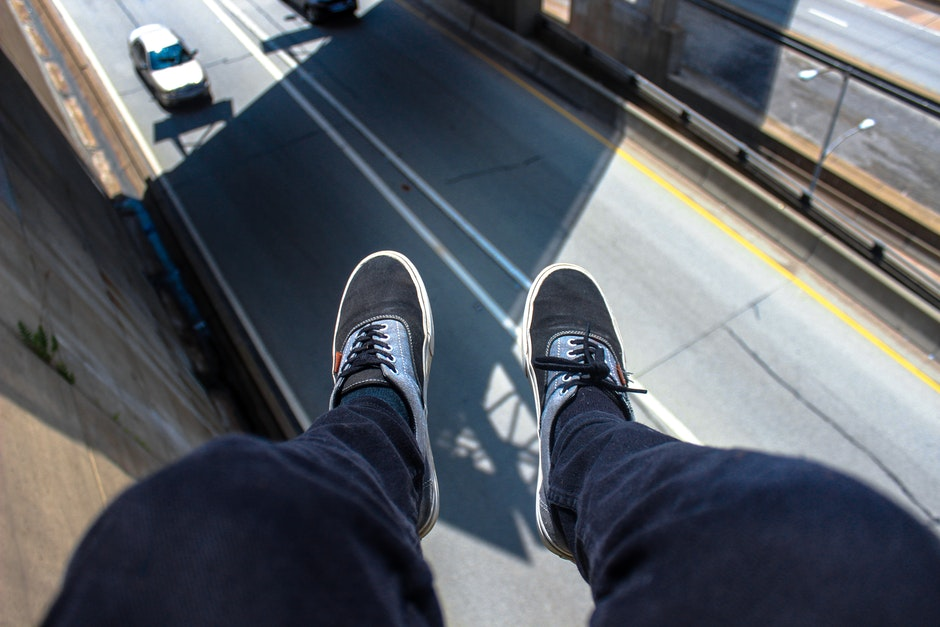 Man in Blue Pants Wearing Black and White Lace Up Low Top Sneakers