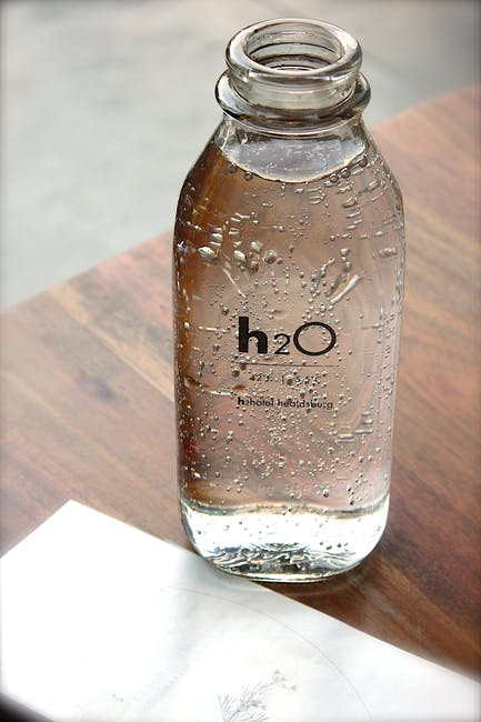 Image of a clear glass bottle containing water sitting on a table. Make sure you pack enough for your road trip