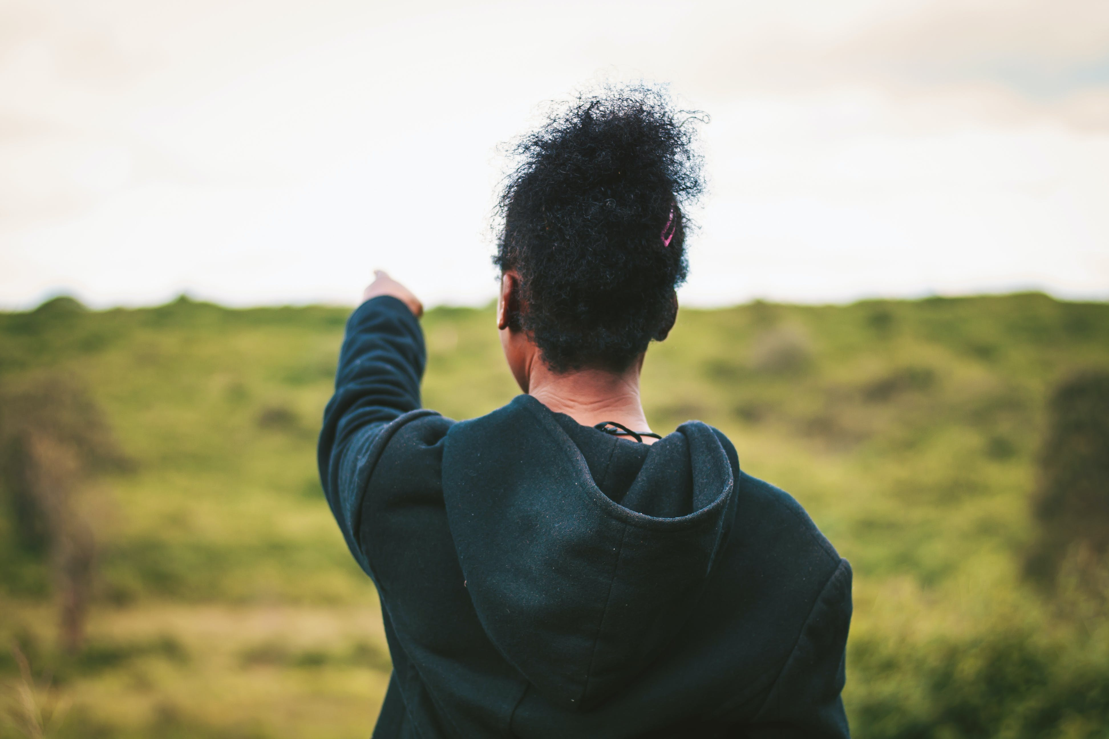 Man Pointing on Grass Field