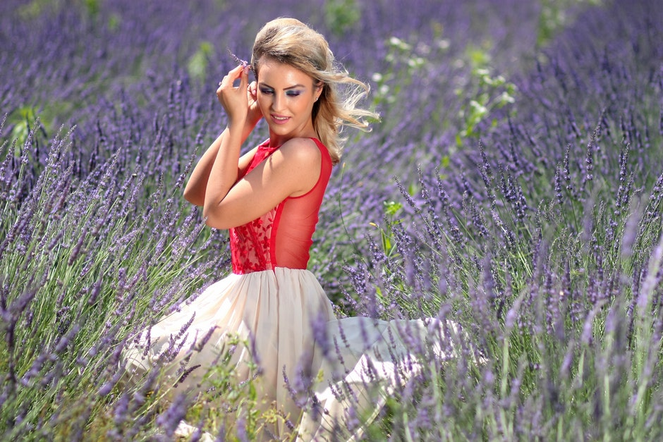 Woman in Red Tank Top With White Mini Skirt Sitting on Grape Purple Hyacinth Field during Daytime
