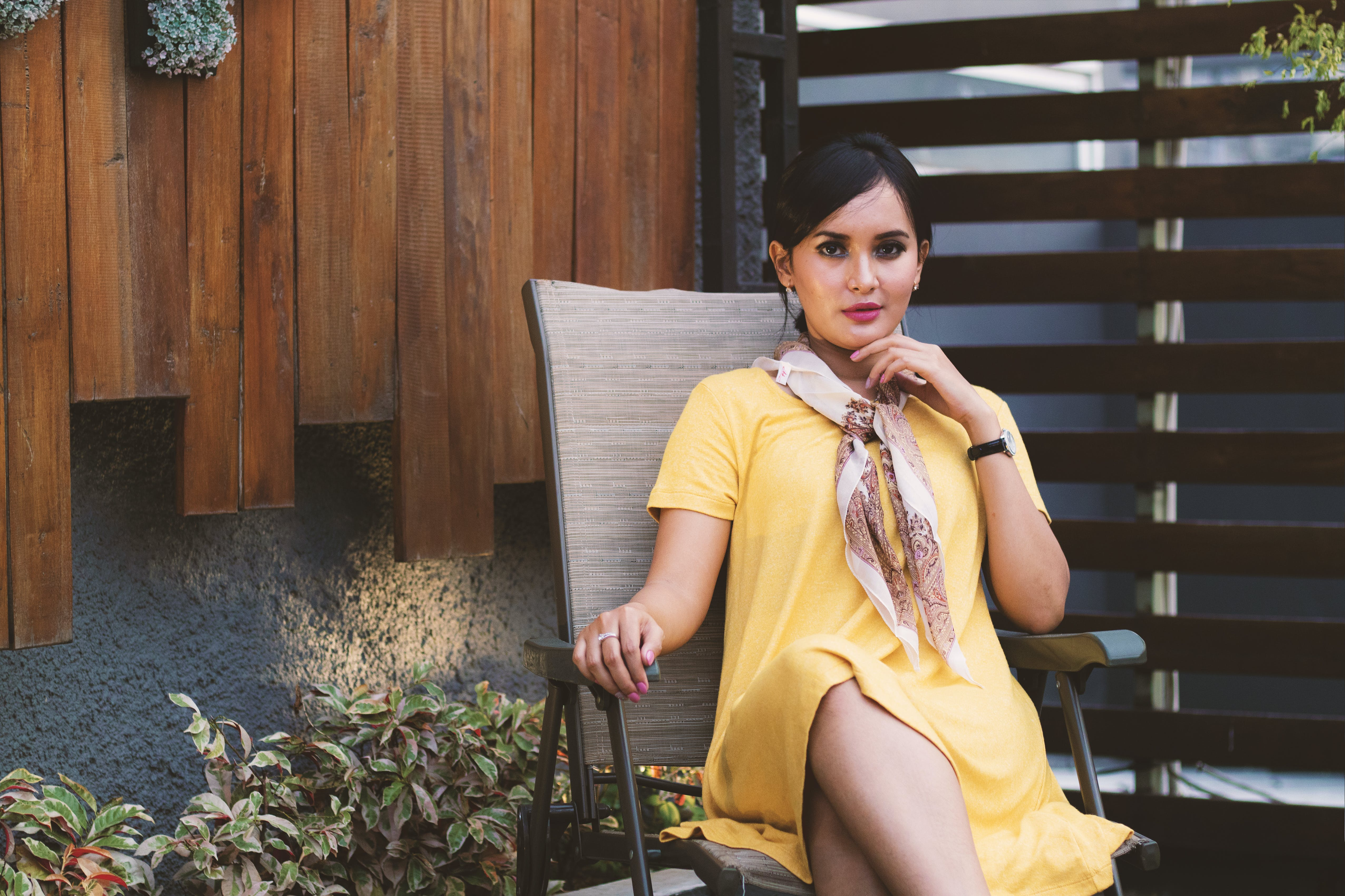 Woman Wearing Yellow Short-sleeved dress Sitting on Black Metal Armchair