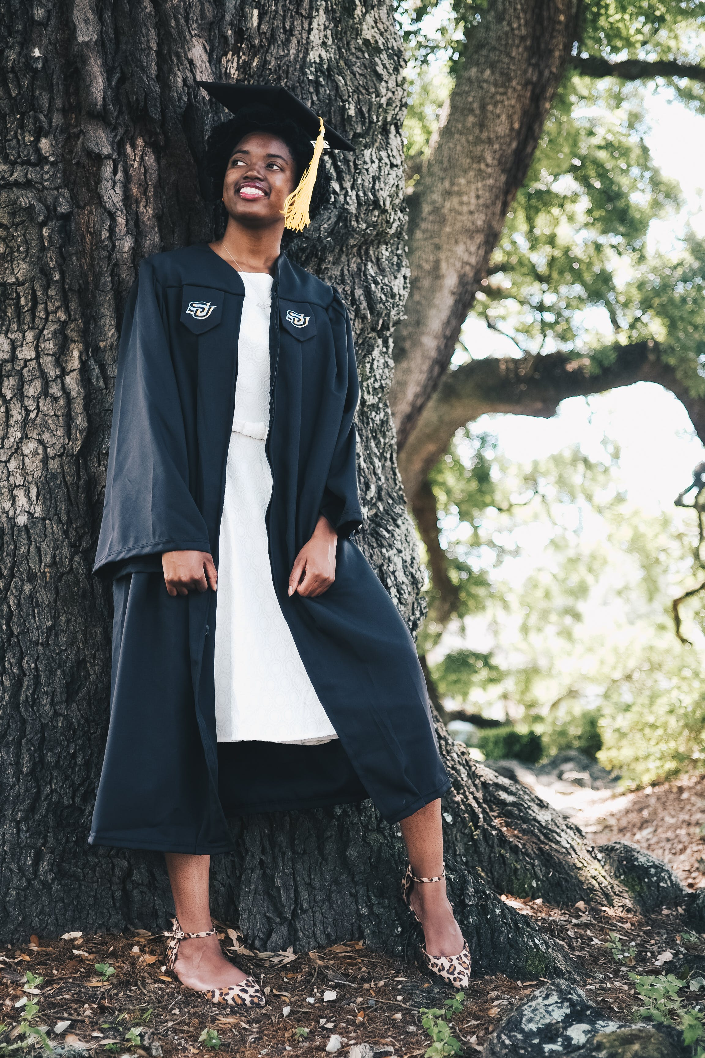 Smiling Woman Wearing Black Academic Gown and Hat Leaning Behind Tree