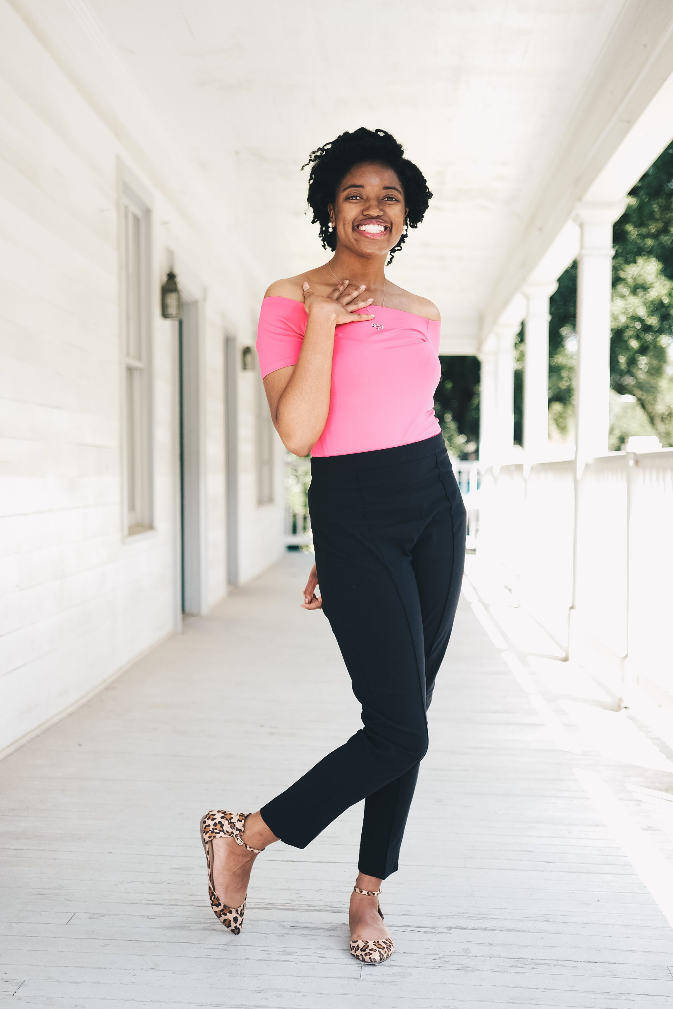 Woman Wearing Pink Off-shoulder Shirt and Black Pants While Standing Near Wall