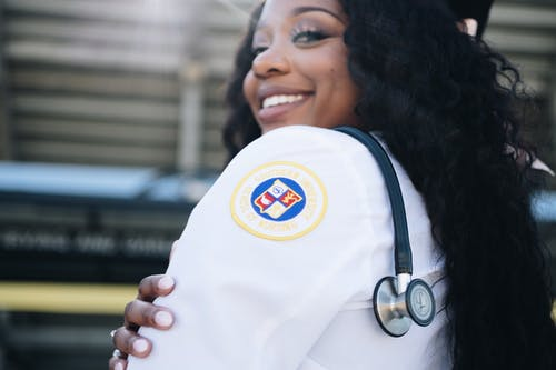 Black woman in medical uniform and stethoscope hanging over shoulder