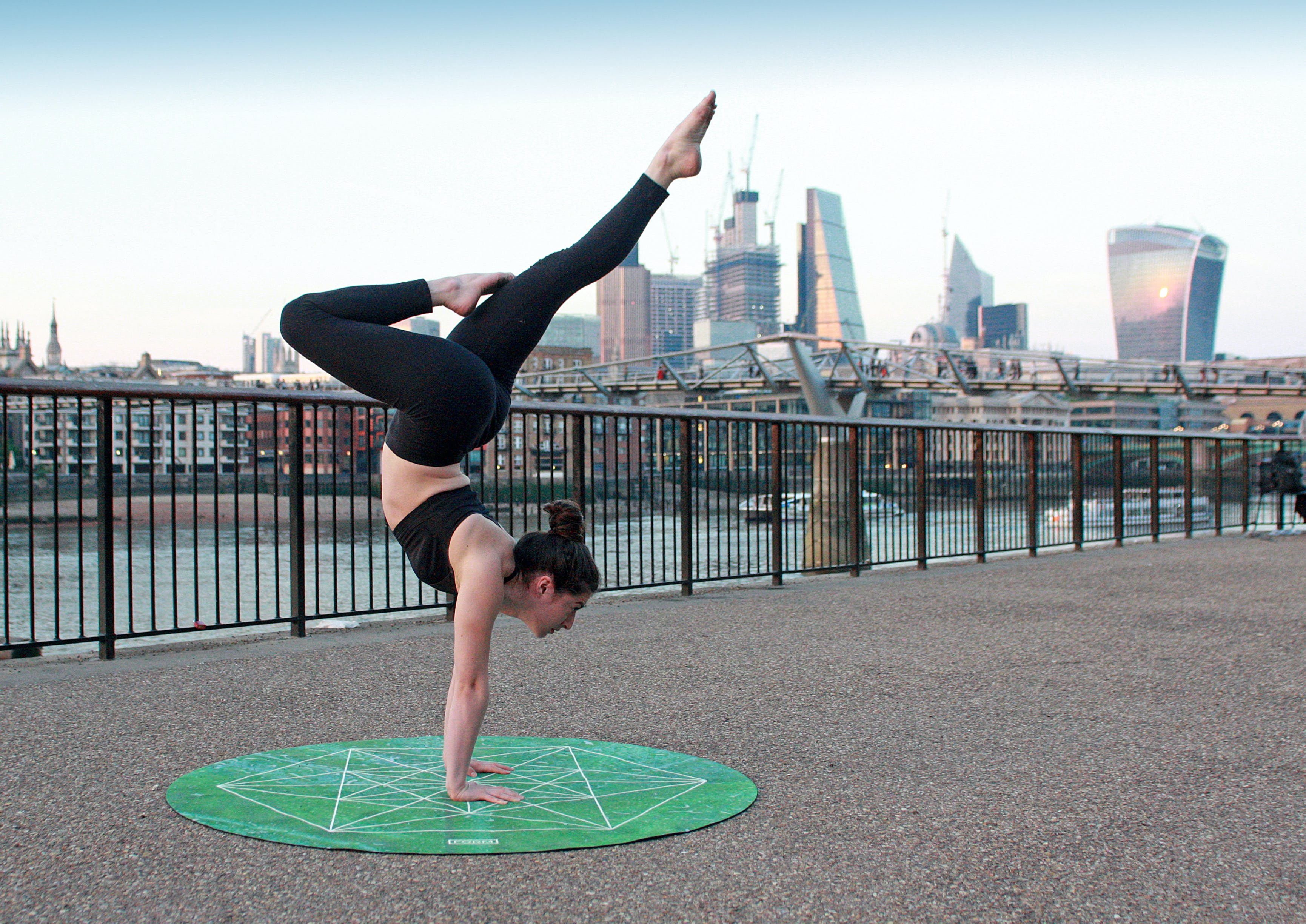 Woman Wearing Black Top And Leggings On Green Yoga Mat