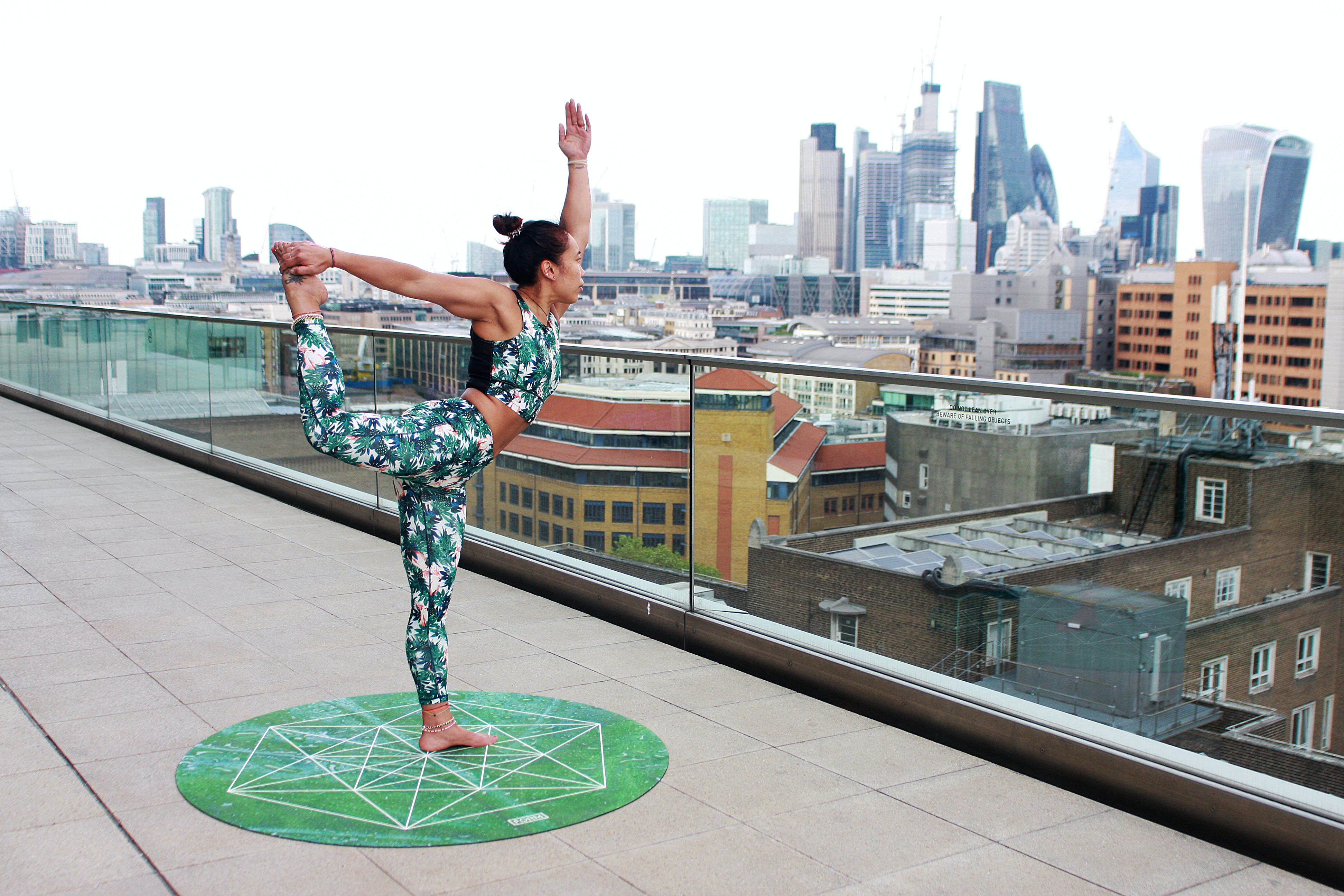 Woman on Round Green Yoga Mat Position in Right Leg High and Left Hand Upright Posiiton