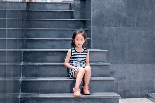 Girl Wearing Black and White Striped Dress Sitting on Stair