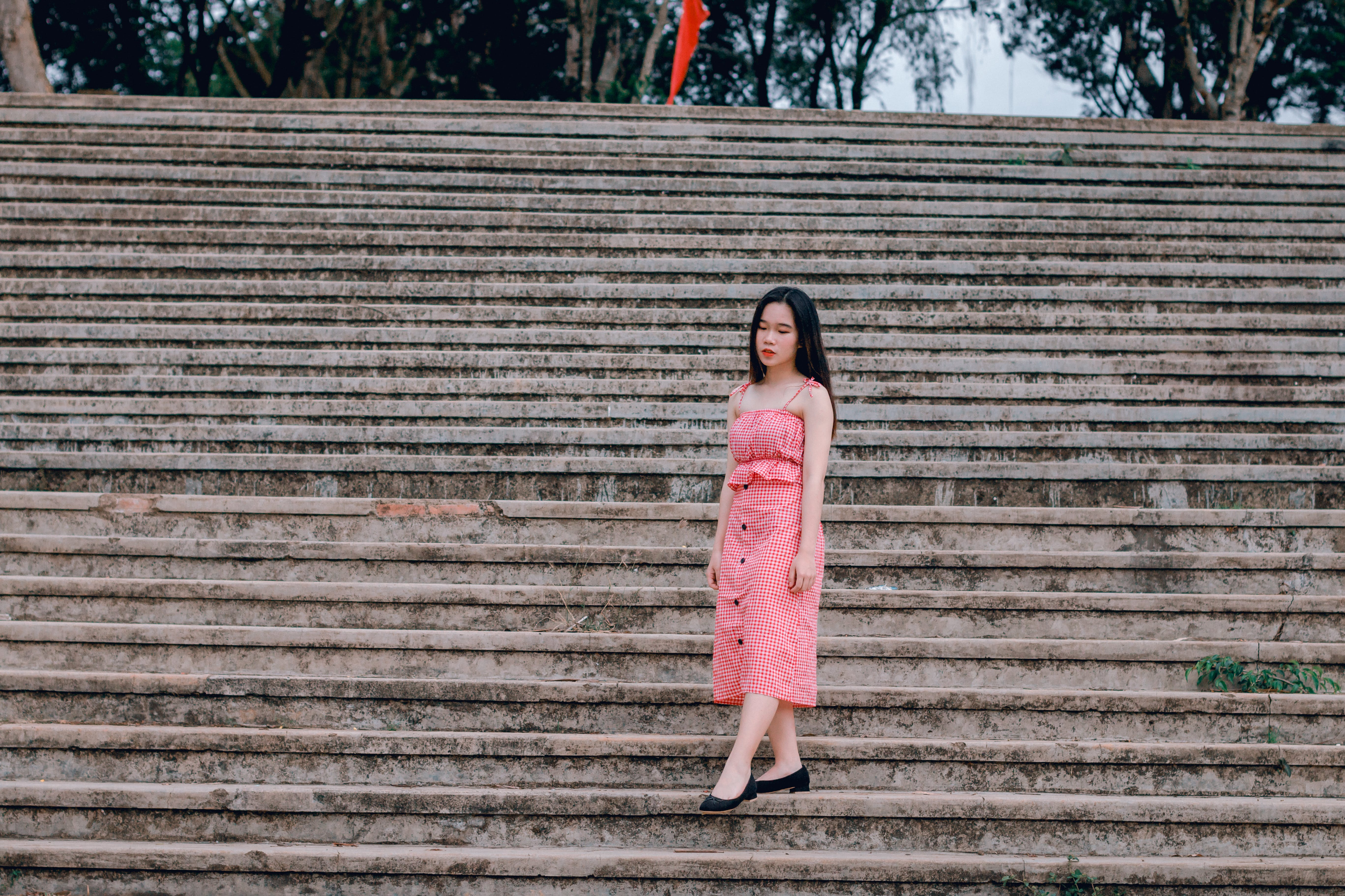 Woman Wearing Pink Spaghetti-strap Dress Standing on Grey Concrete Stairs