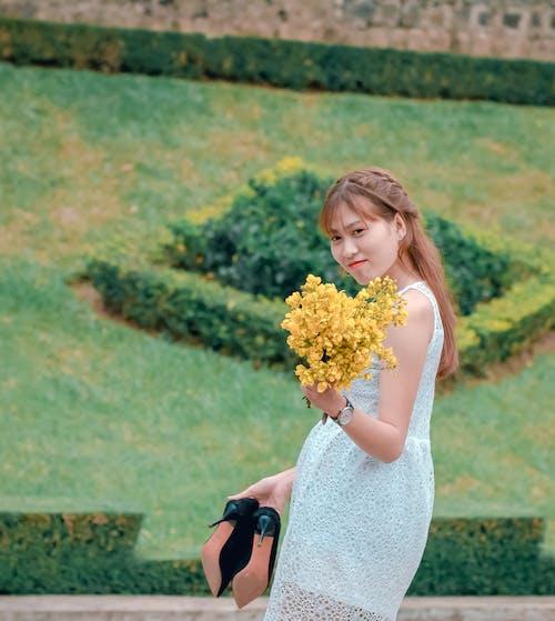 Wanita Mengenakan Gaun Renda Putih Memegang Buket Bunga Kuning