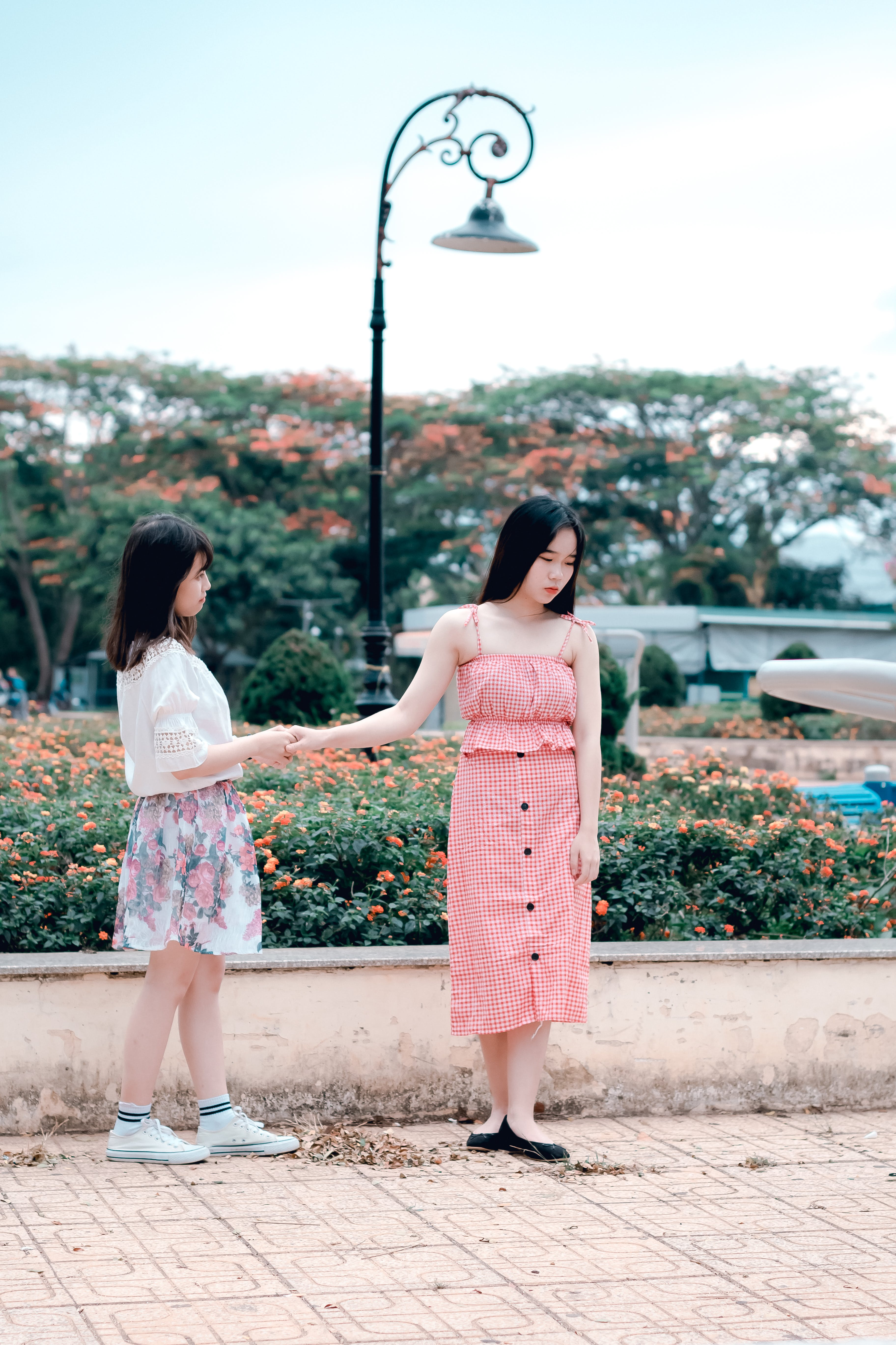 Two Women Holding Hands Under Green Metal Post Lamp
