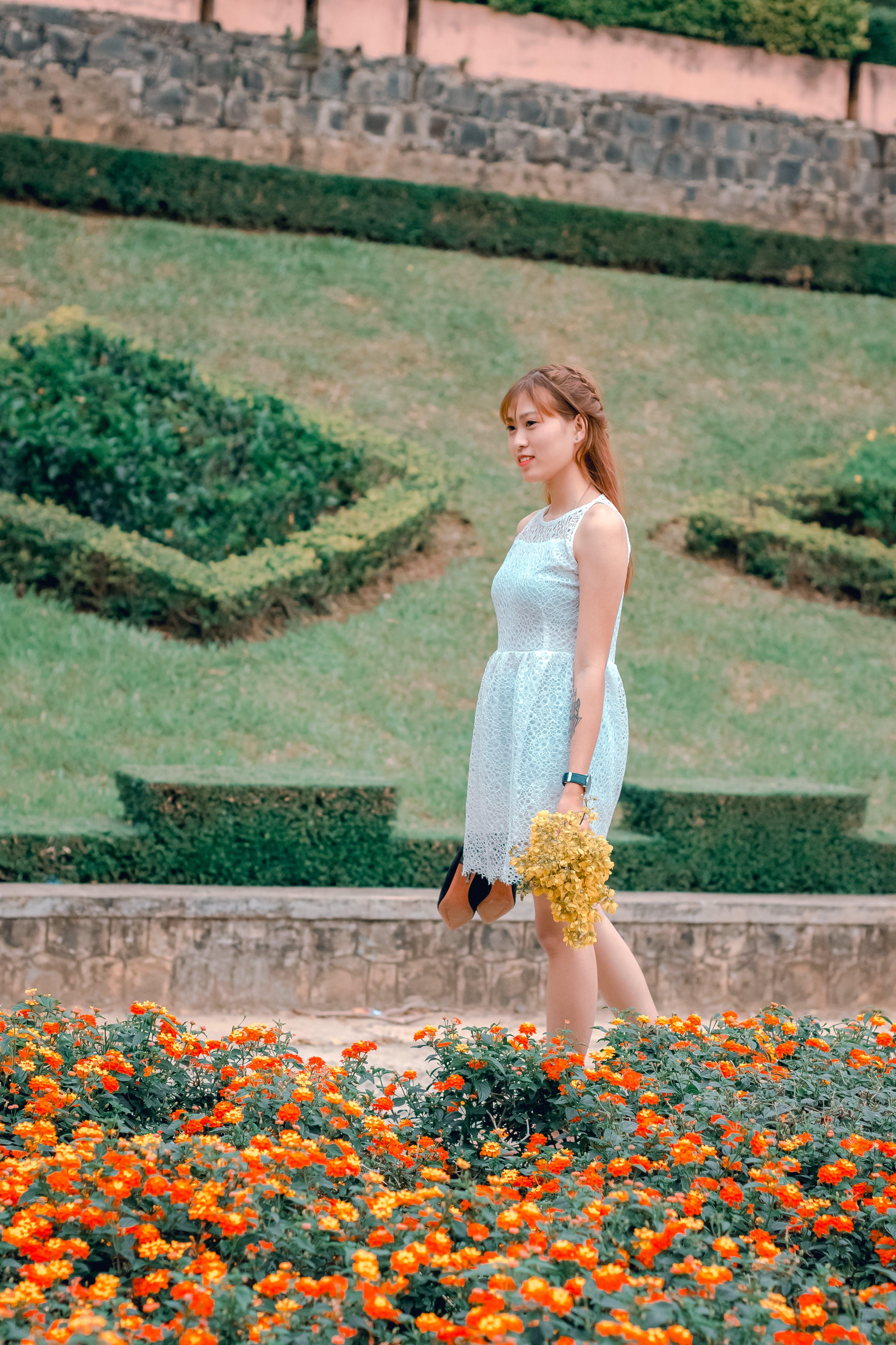 Women's White Sleeveless Dress Holding Yellow Flowers