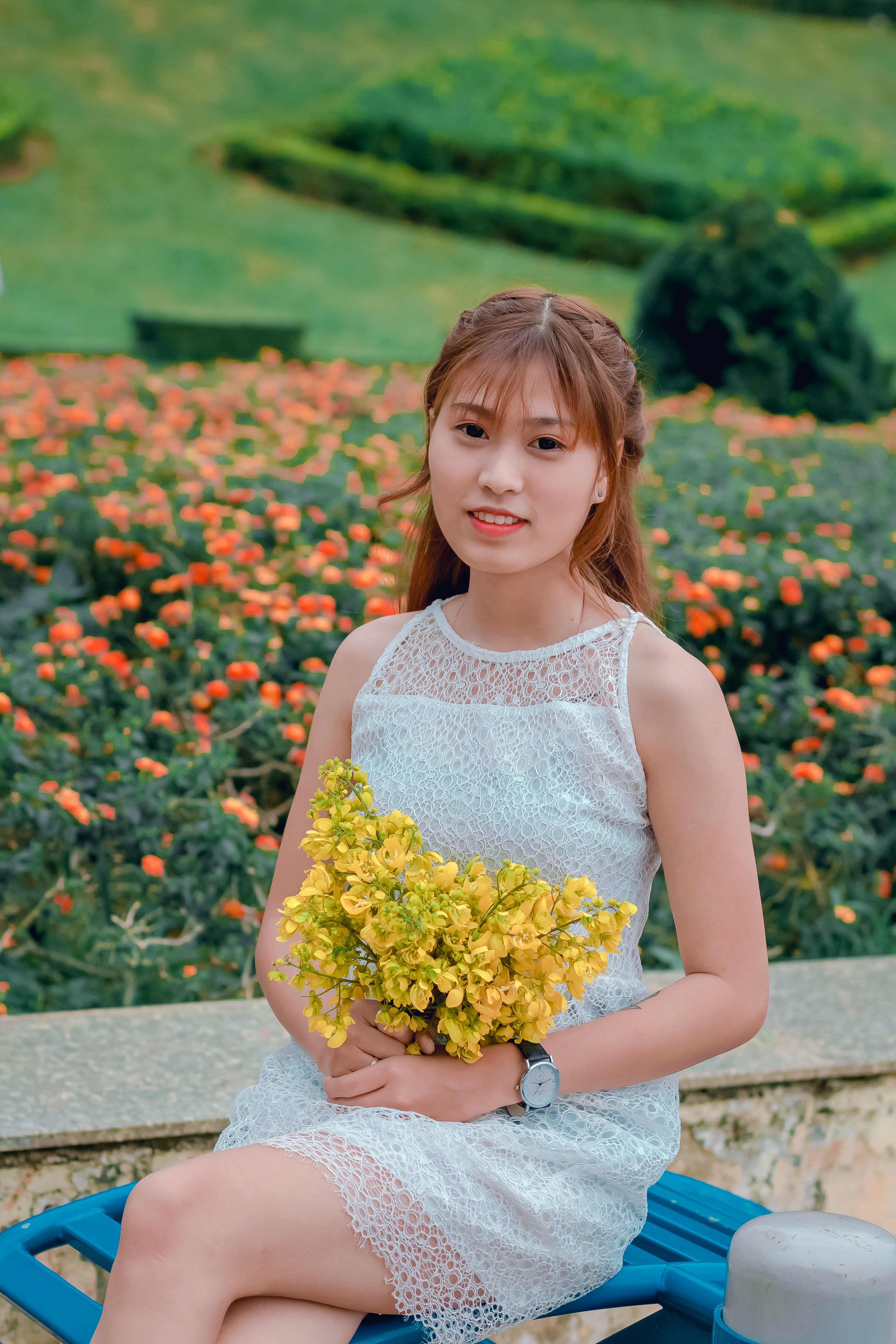 Focus Photo of Woman Wearing Dress While Holding Bouquet of Yellow Flowers