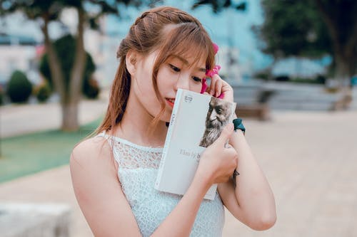 Woman Wearing White Sleeveless Top Holding Book