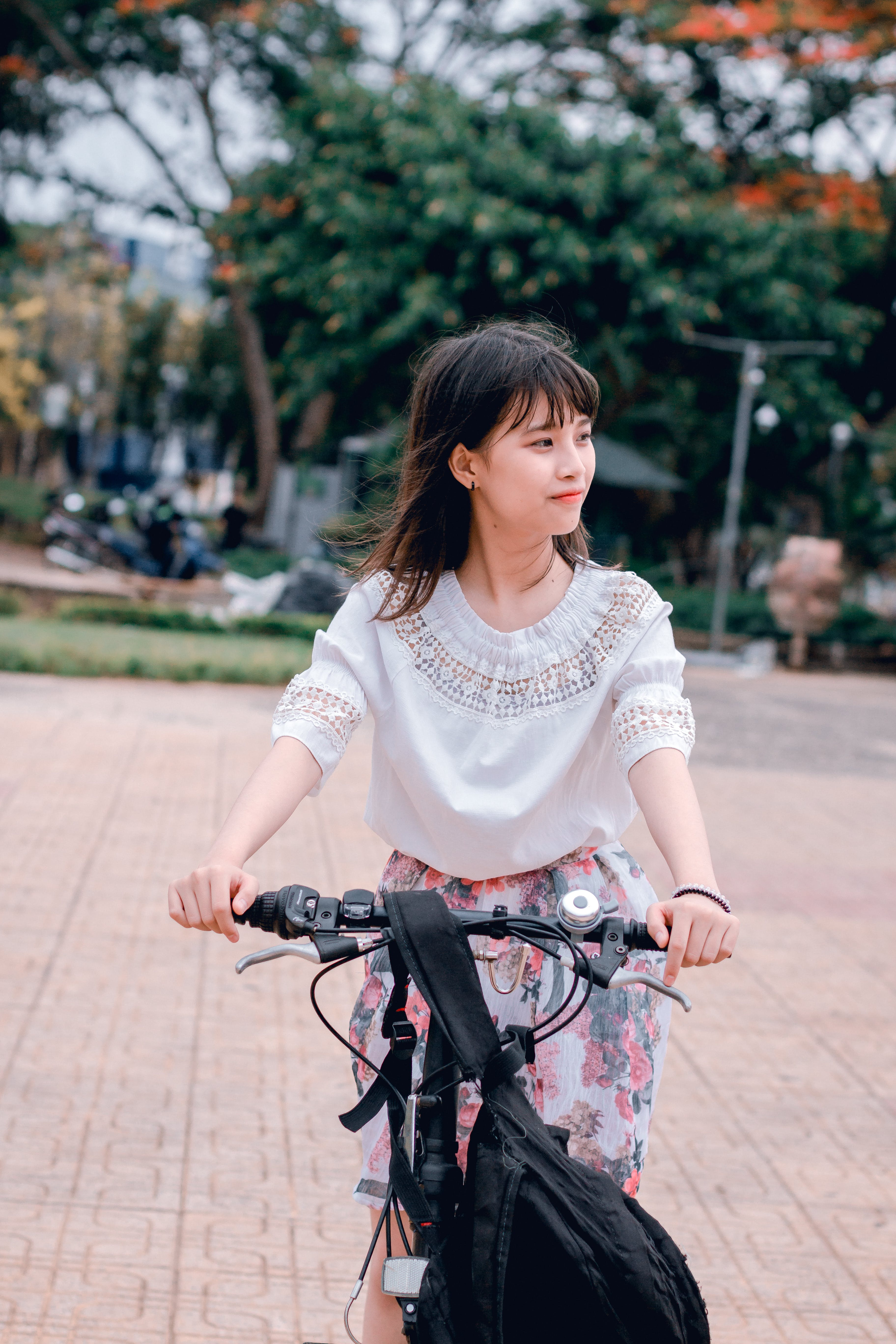 Woman Wearing White Blouse Riding Bicycle on Brown Concrete Tiled Area Near Trees