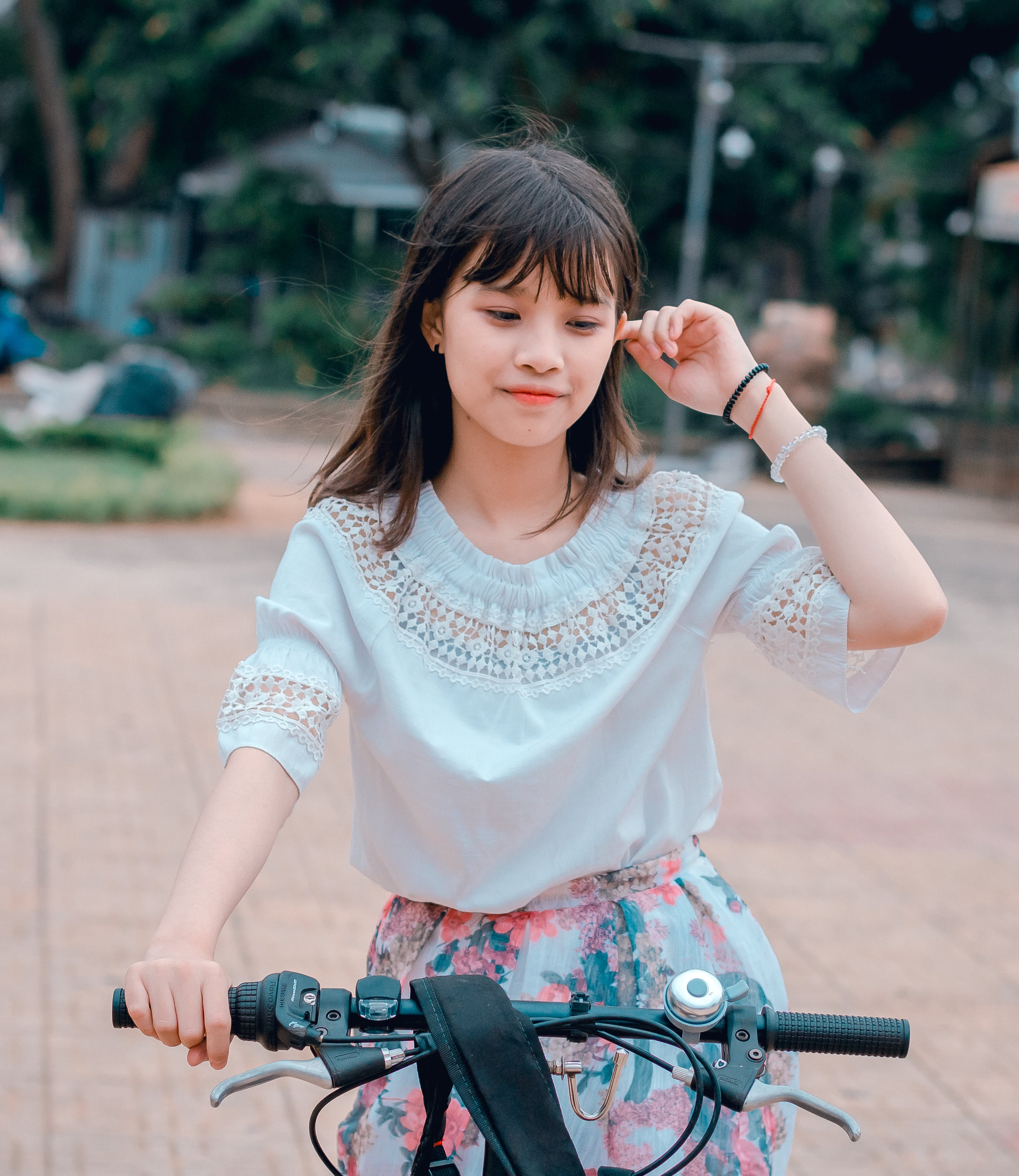 Woman Wearing White Blouse and Multicolored Floral Skirt Riding Bike