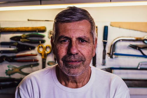 Portrait Photo of Man in White Crew-neck T-Shirt With Assorted Hand Tools in Background