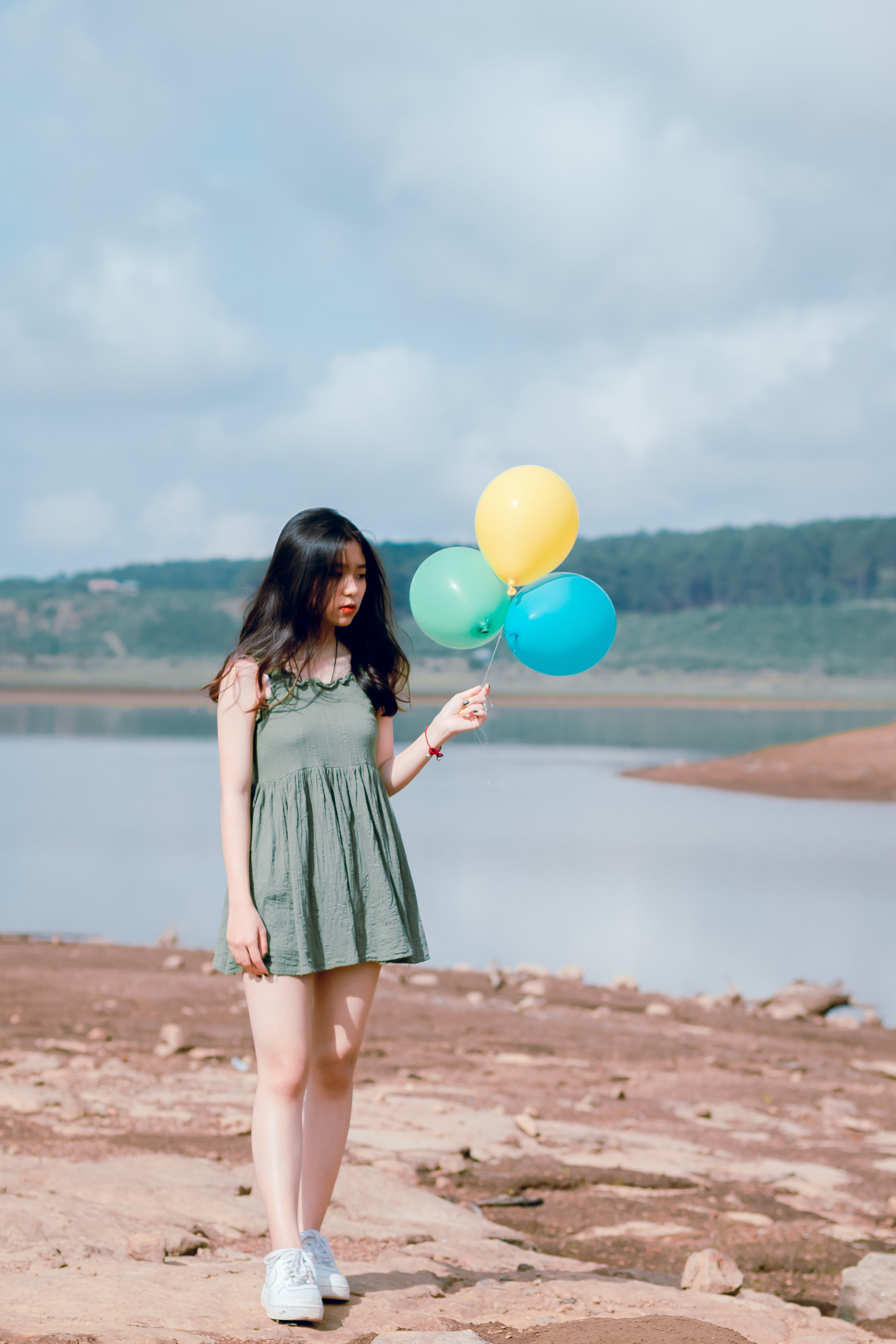 Woman in Green Sleeveless Dress Holding Balloons