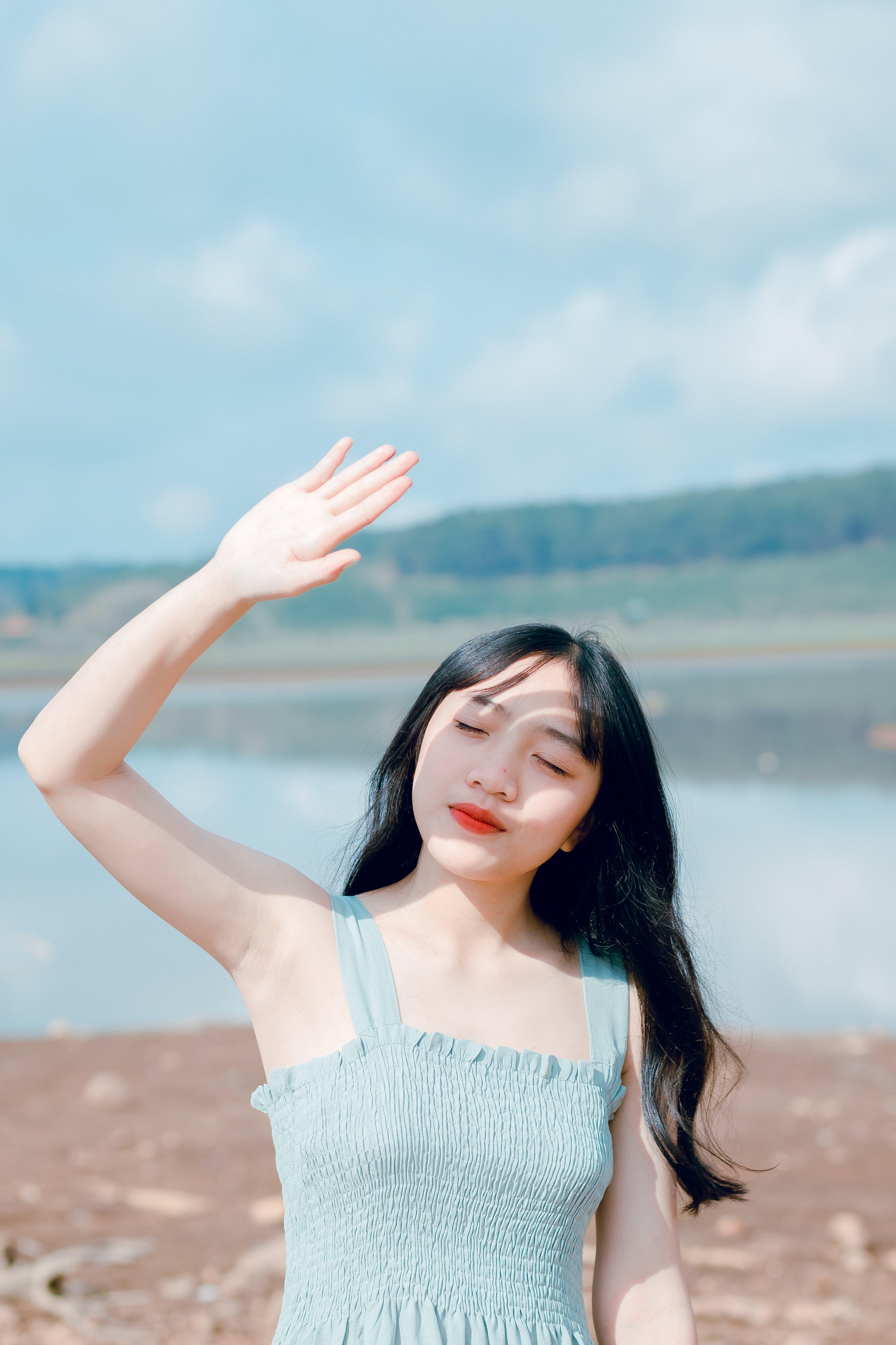 Woman Raising Hand To Cover Sunlight
