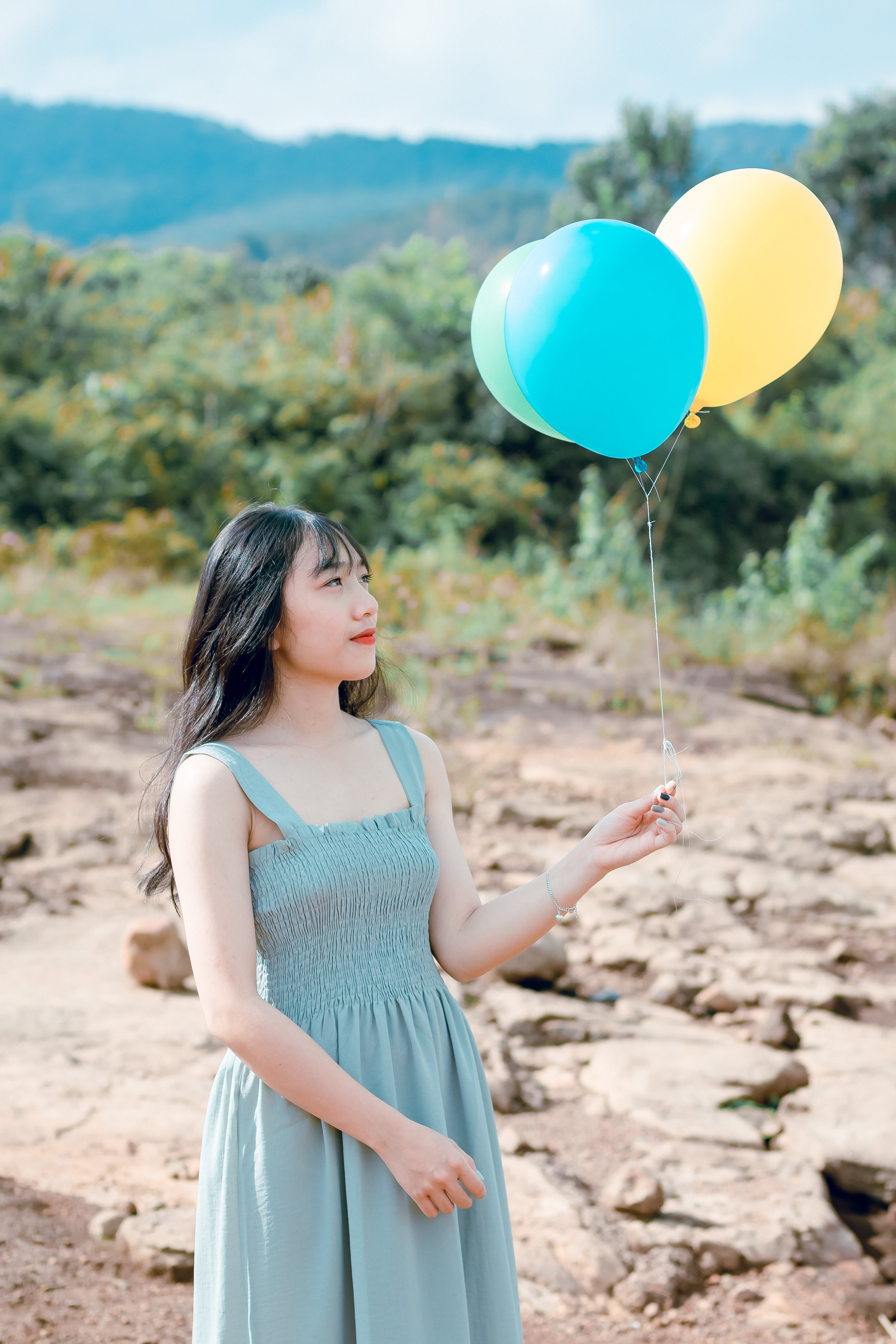 Woman Wearing Blue Dress Holding Balloons