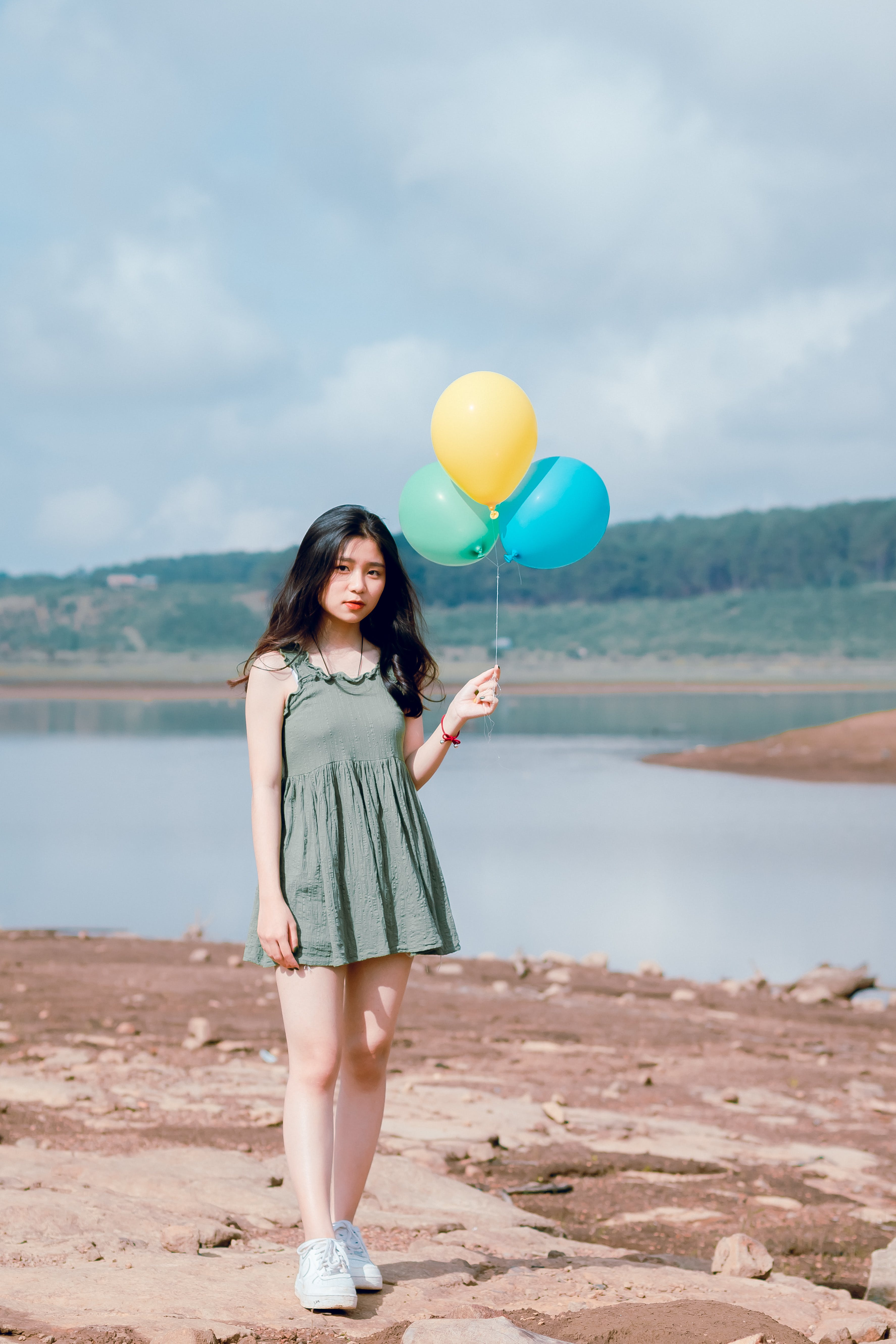 Woman's in Green Sleeveless Dress Holding 3 Balloons
