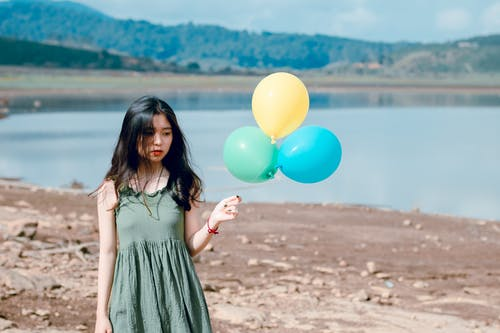 Woman in Green Sleeveless Dress Holding Three Balloons