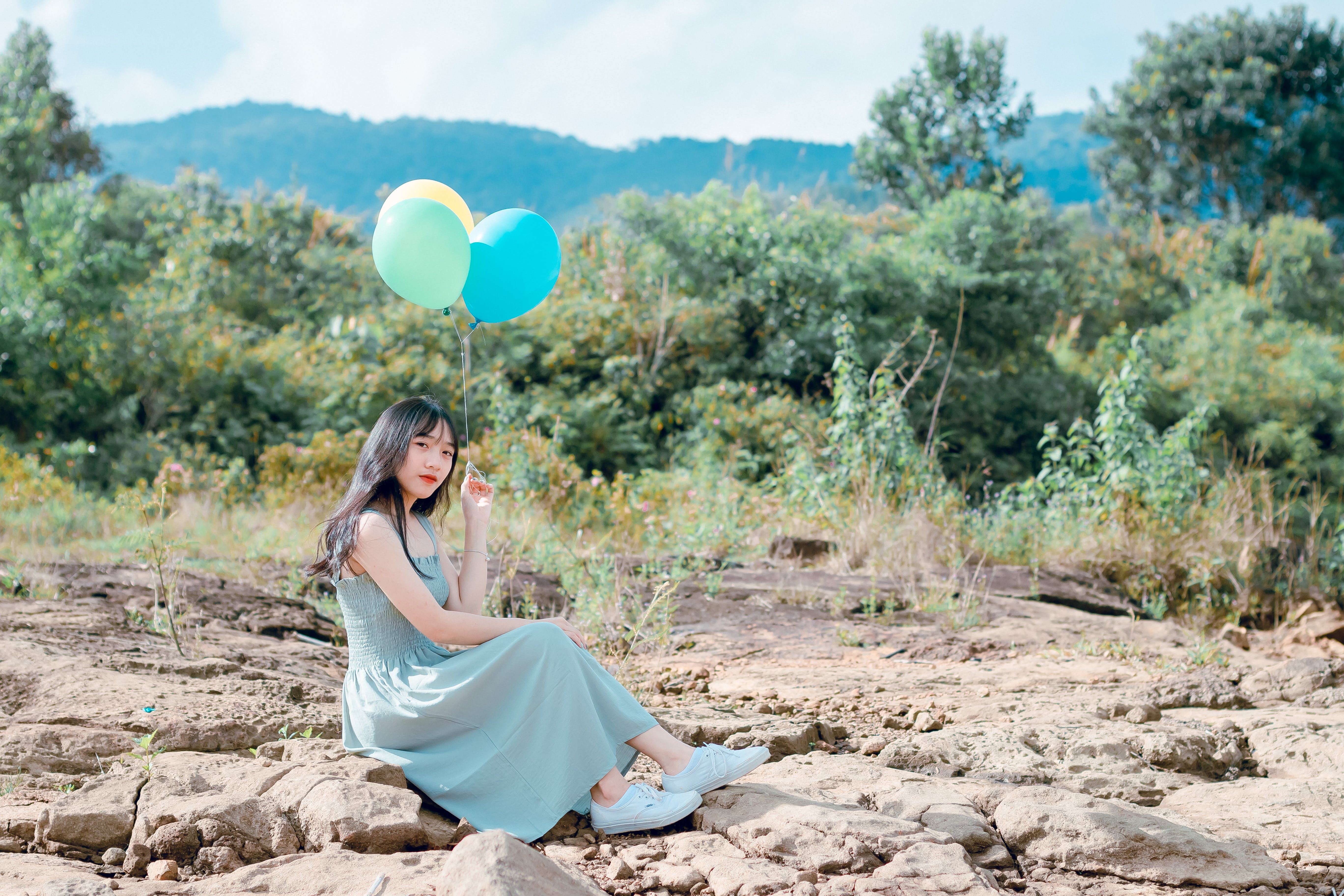 Woman Sitting On Rocks Holding Balloons