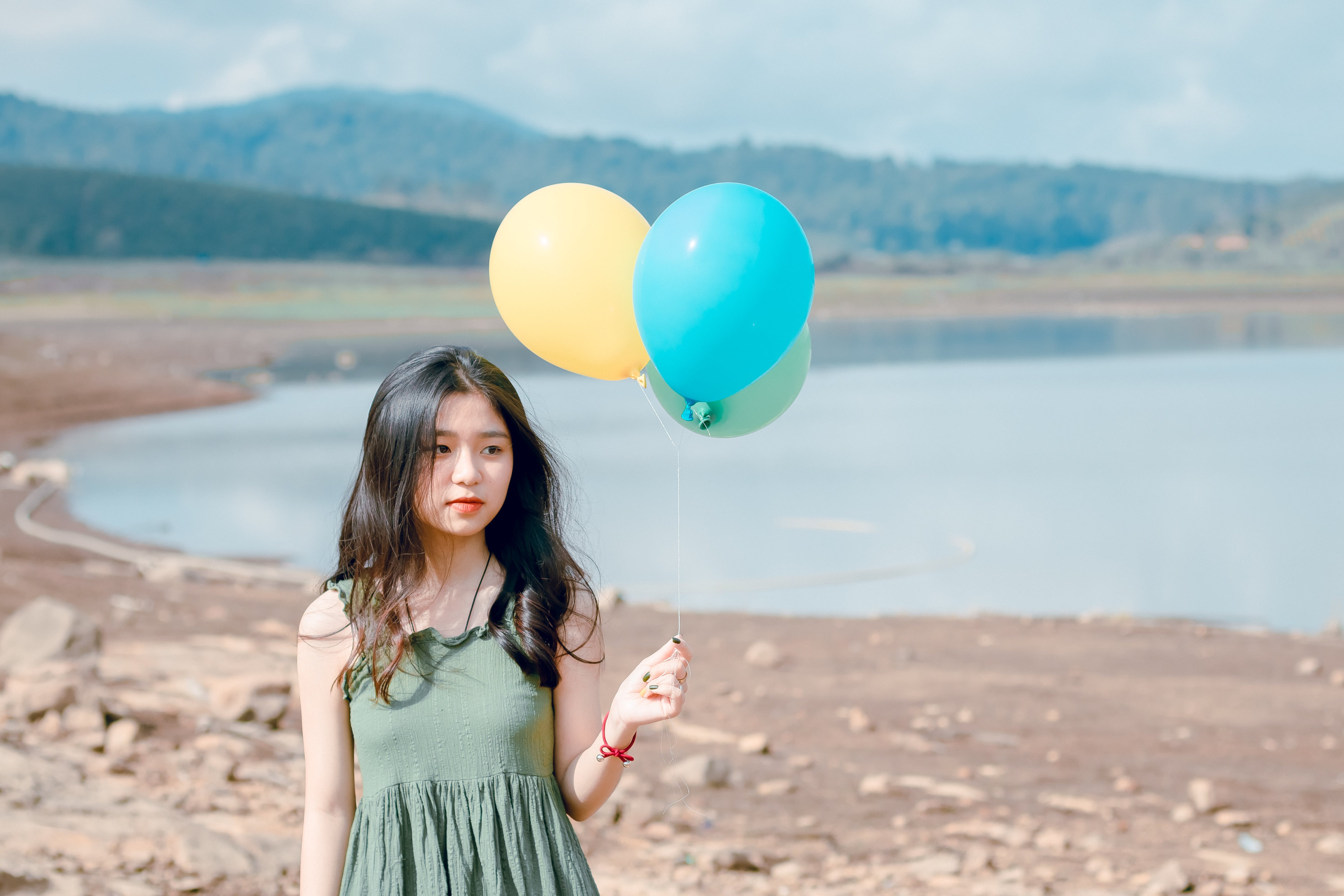 Shallow Focus Photography of Woman Holding Three Assorted-color Balloons