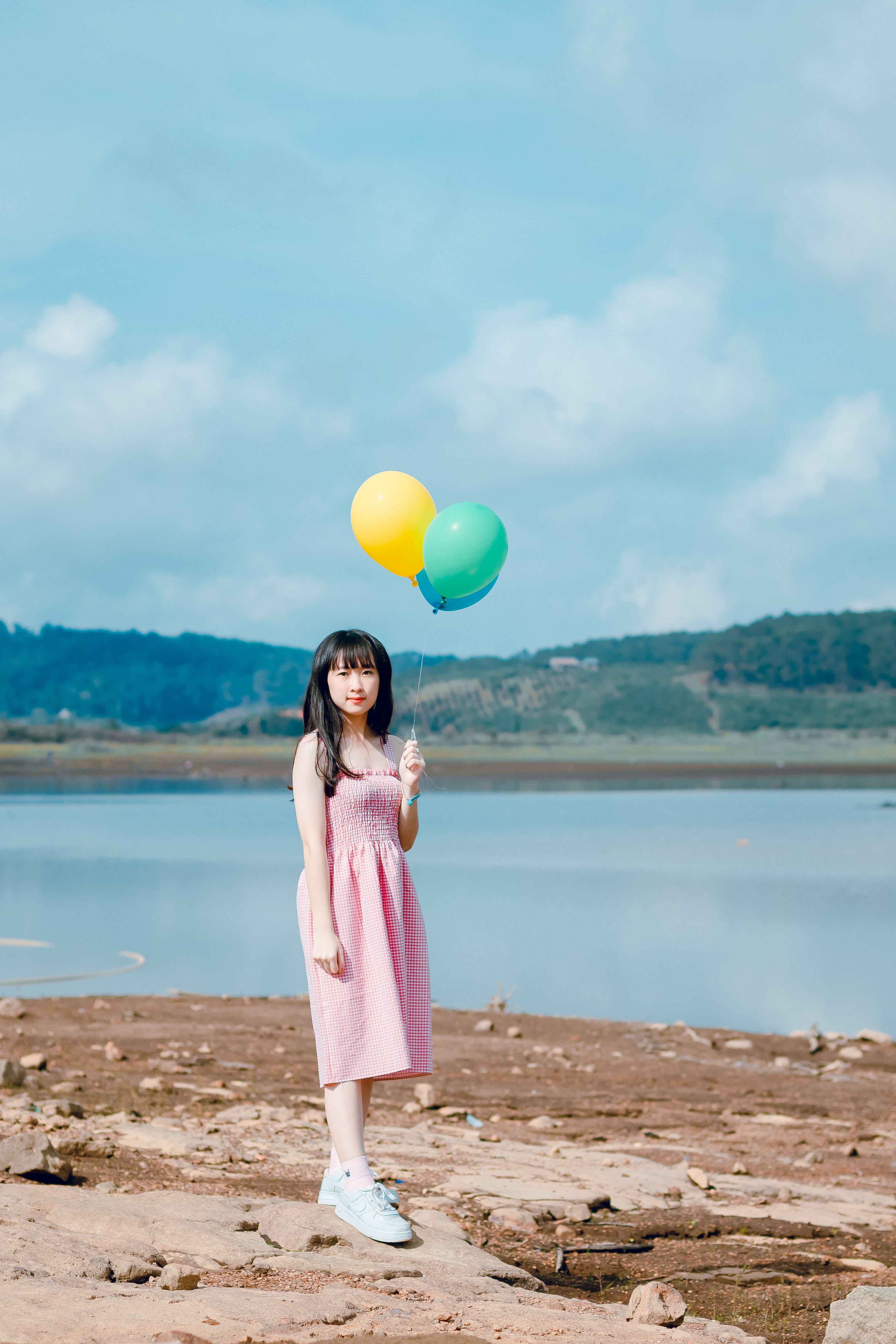 Woman Holding Balloons Standing on Beige Sand