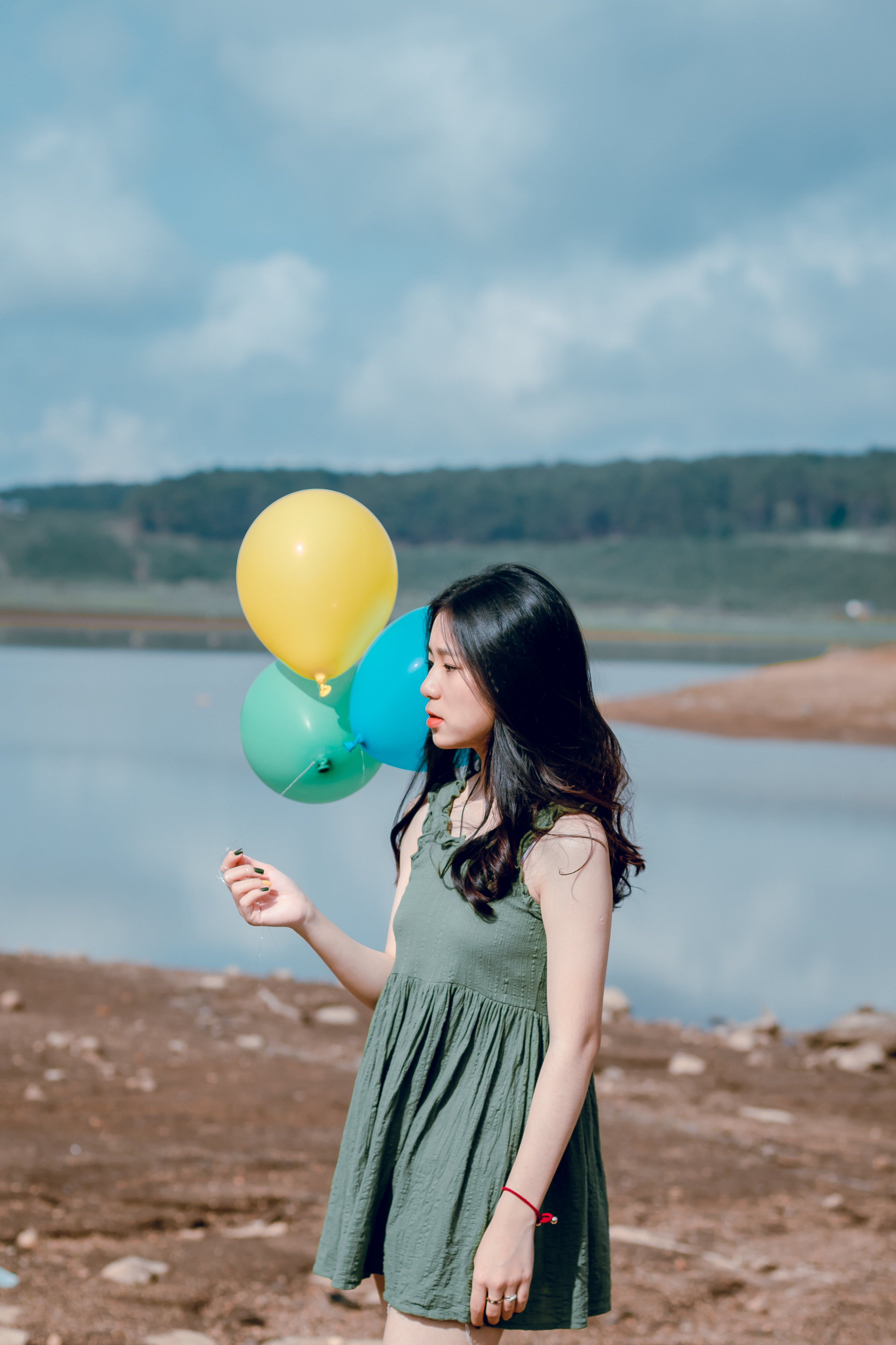 Woman in Green Sleeveless Dress Holding Yellow, Green, and Blue Balloons