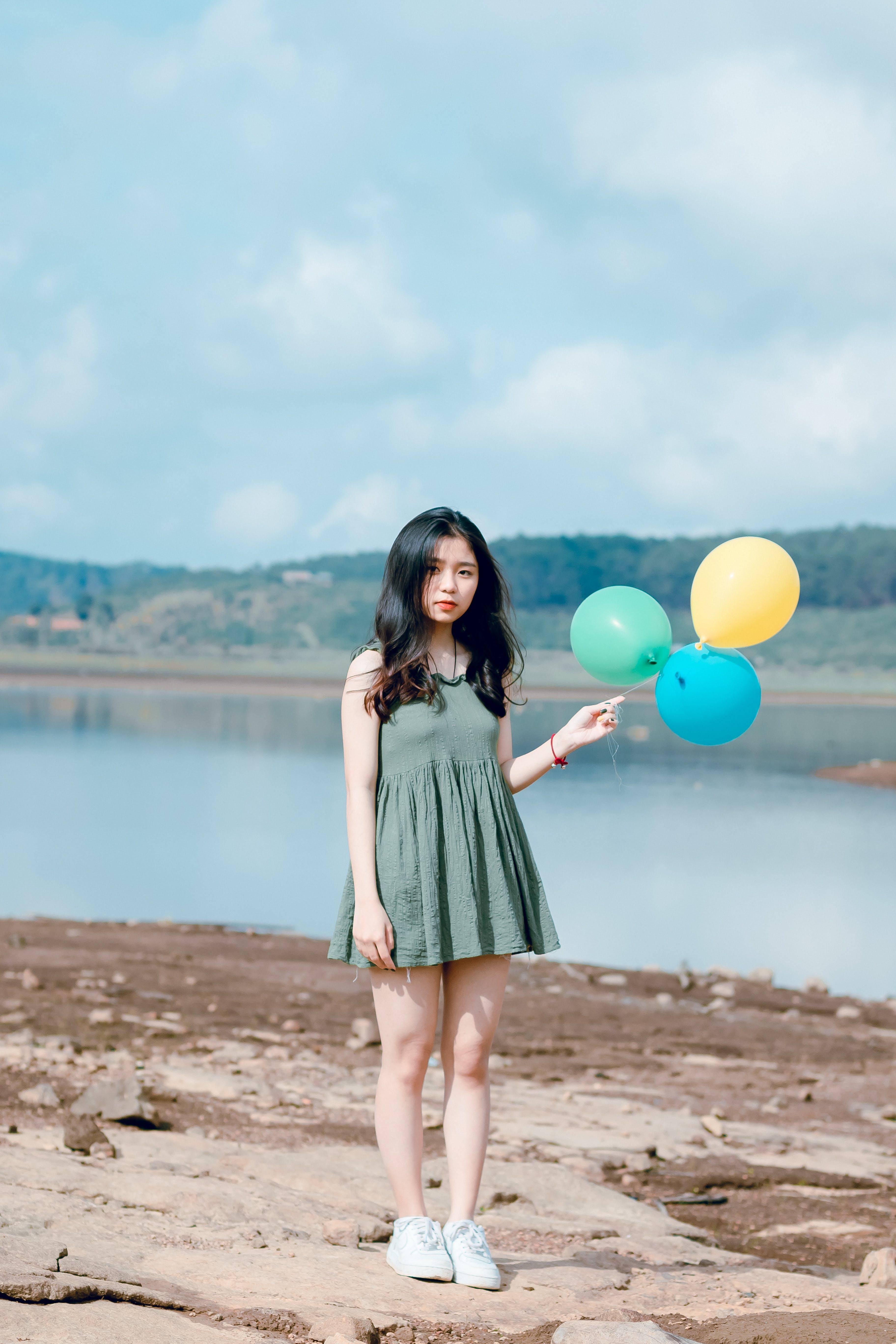 Photo of Girl Wearing Green Mini Dress Holding Balloons
