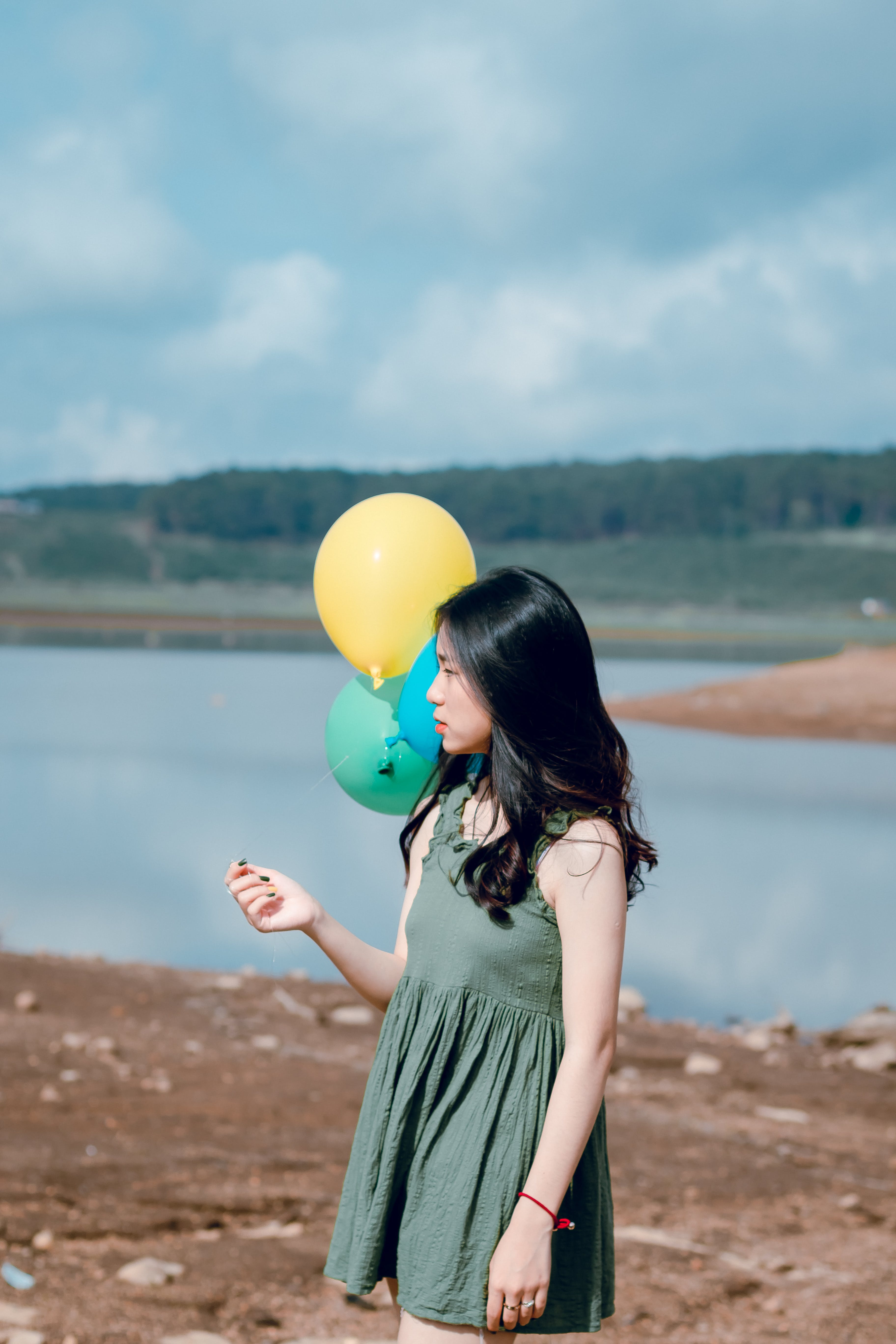 Woman in Green Crew-neck Sleeveless Mini Dress Holding Balloons Near Body of Water